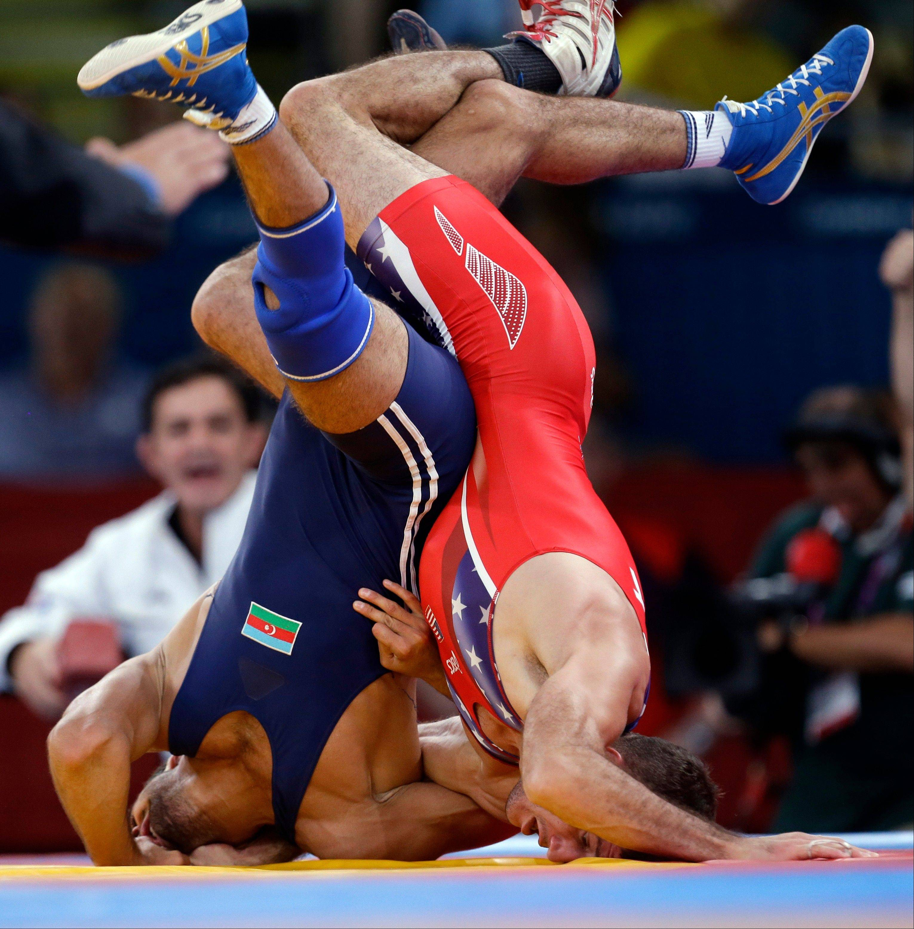 Coleman Scott of the United States competes against Toghrul Asgarov of Azerbaijan (in blue) during the men's 60-kg freestyle wrestling competition at the 2012 Summer Olympics, Saturday, Aug. 11, 2012, in London.