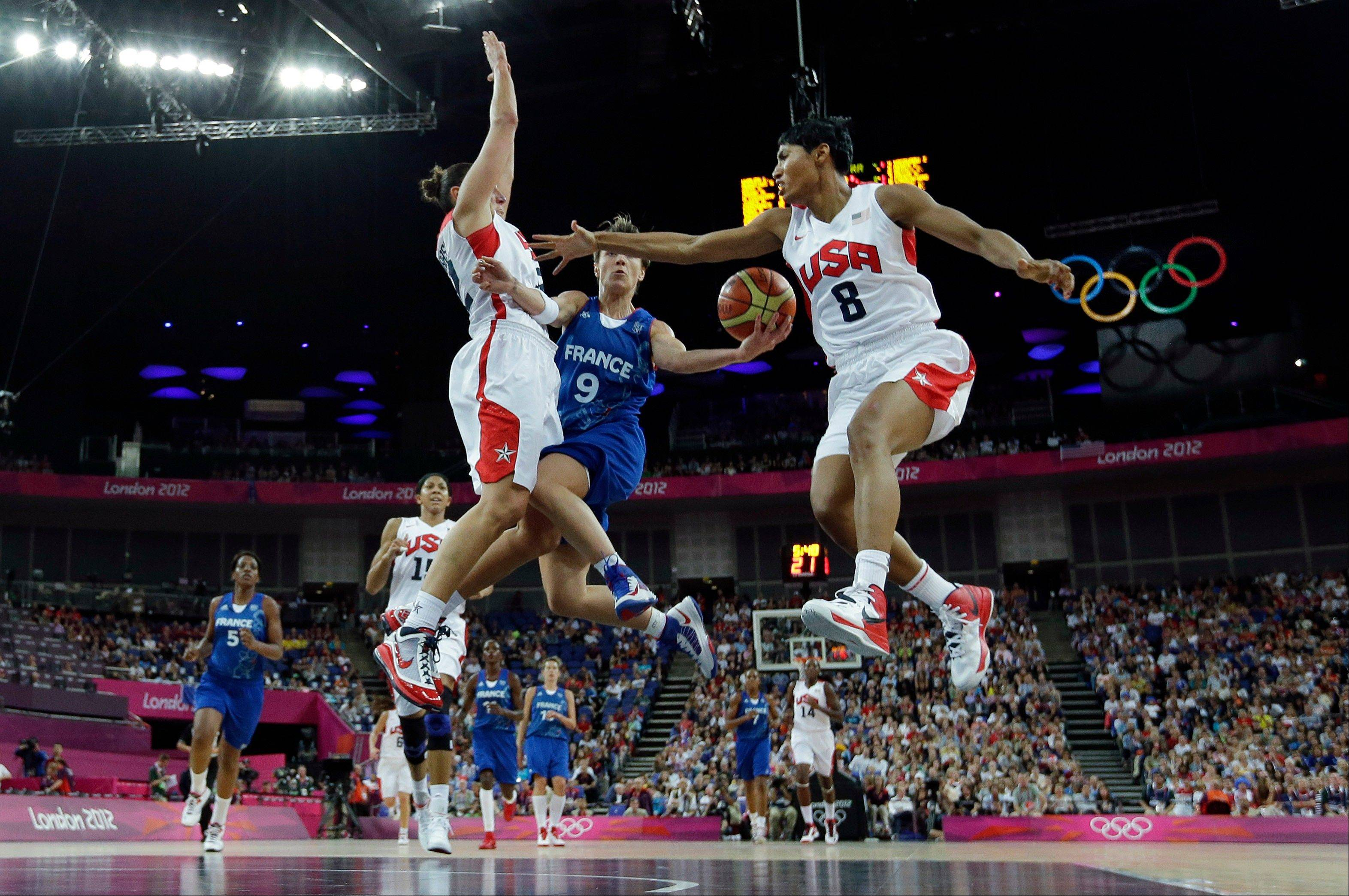 France's Celine Dumerc (9) drives to the basket as United States' Diana Taurasi, left, and Angel McCoughtry (8) defend during a women's gold medal basketball game at the 2012 Summer Olympics, Saturday, Aug. 11, 2012, in London.