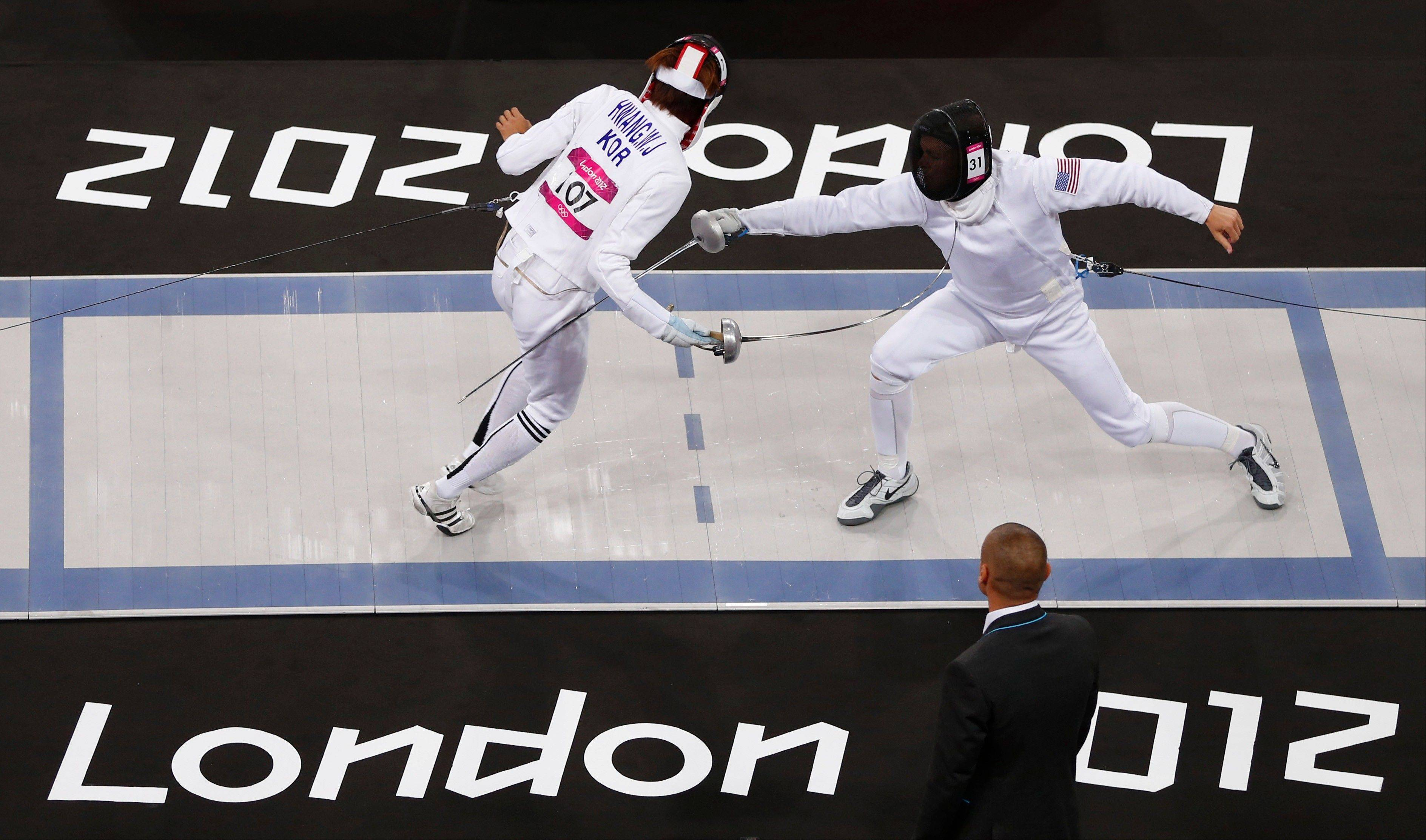Hwang Woojin of South Korea, left, defeats Dennis Bowseher of the United States during the men's fencing section of the modern pentathlon at the 2012 Summer Olympics, Saturday, Aug. 11, 2012, in London.