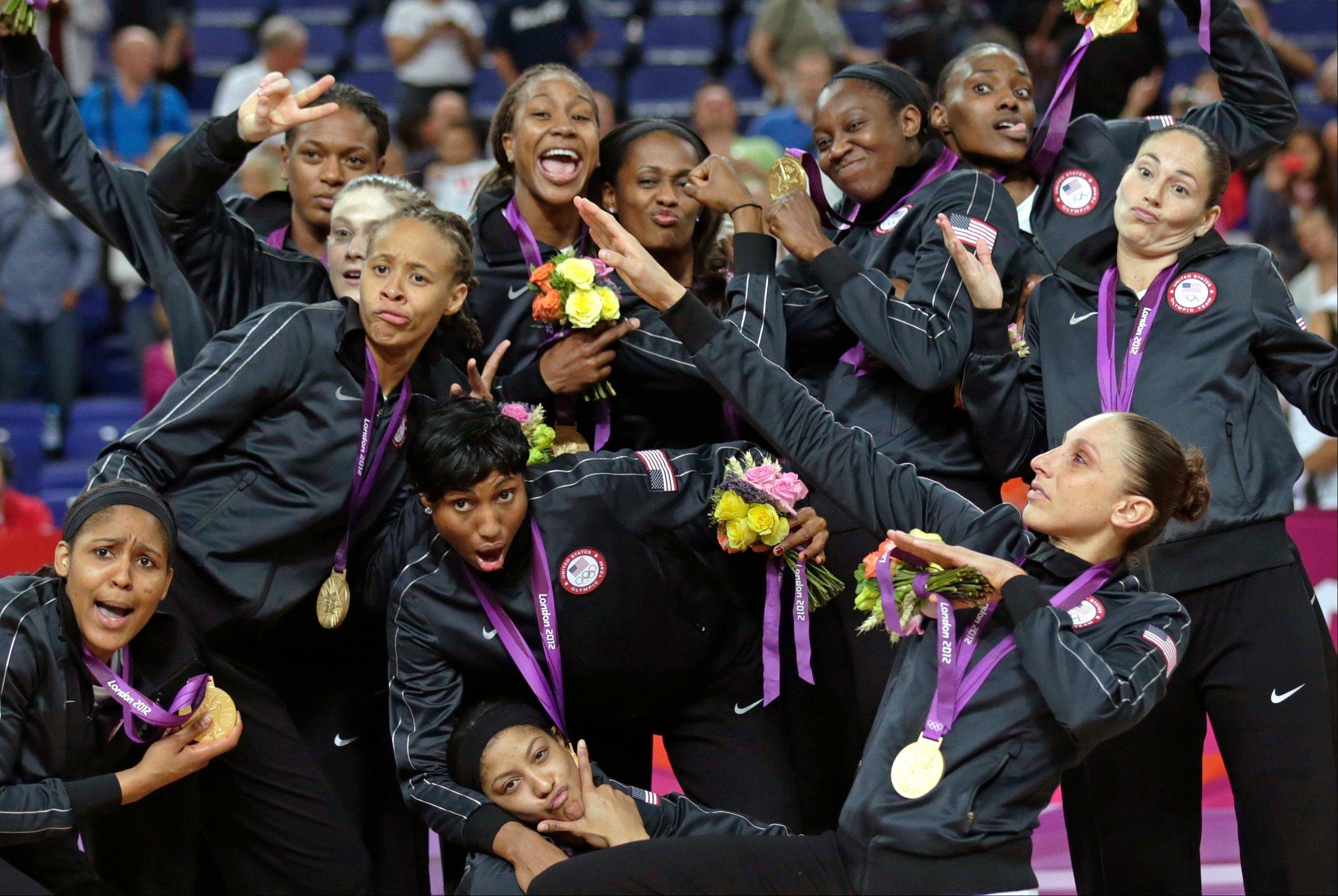 United States' poses with their gold medals at center court after beating France during the women's gold medal basketball game at the 2012 Summer Olympics, Saturday, Aug. 11, 2012, in London.