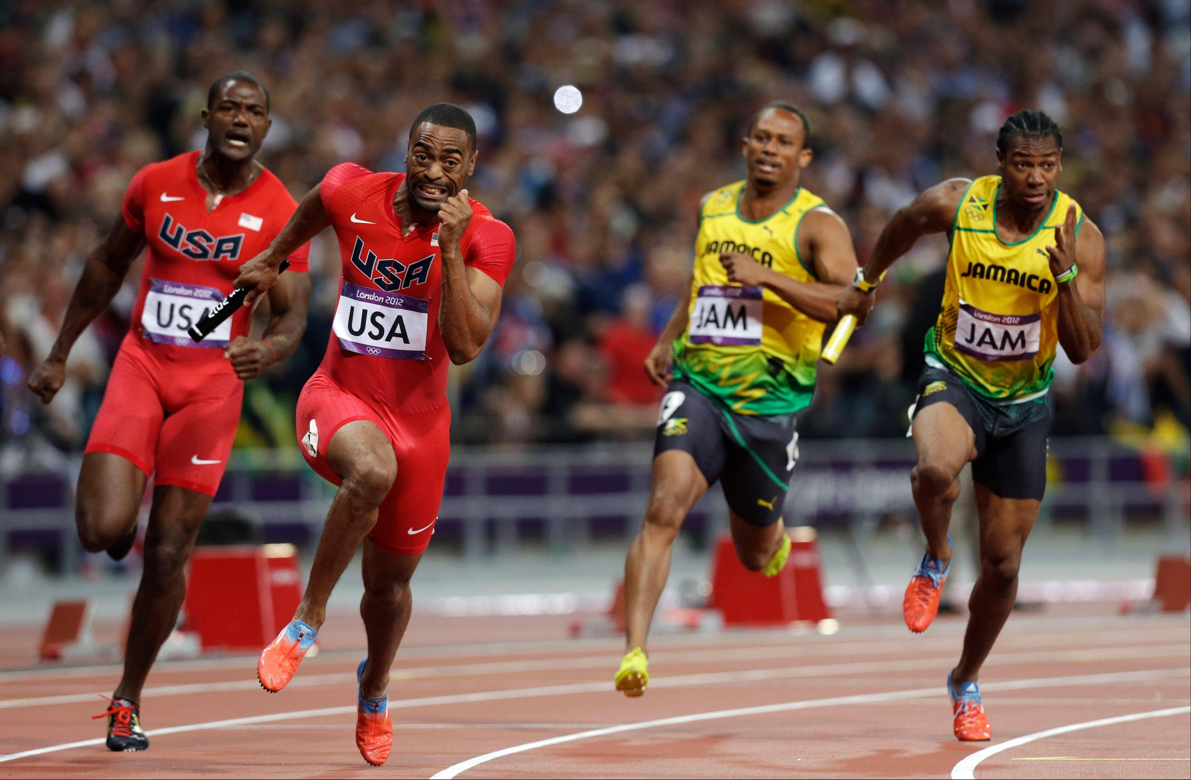 From left, United States' Justin Gatlin hands the baton to Tyson Gay, as Jamaica's Michael Frater hands the baton to Yohan Blake in the men's 4x100-meter relay final during the athletics in the Olympic Stadium at the 2012 Summer Olympics, London, Saturday, Aug. 11, 2012.
