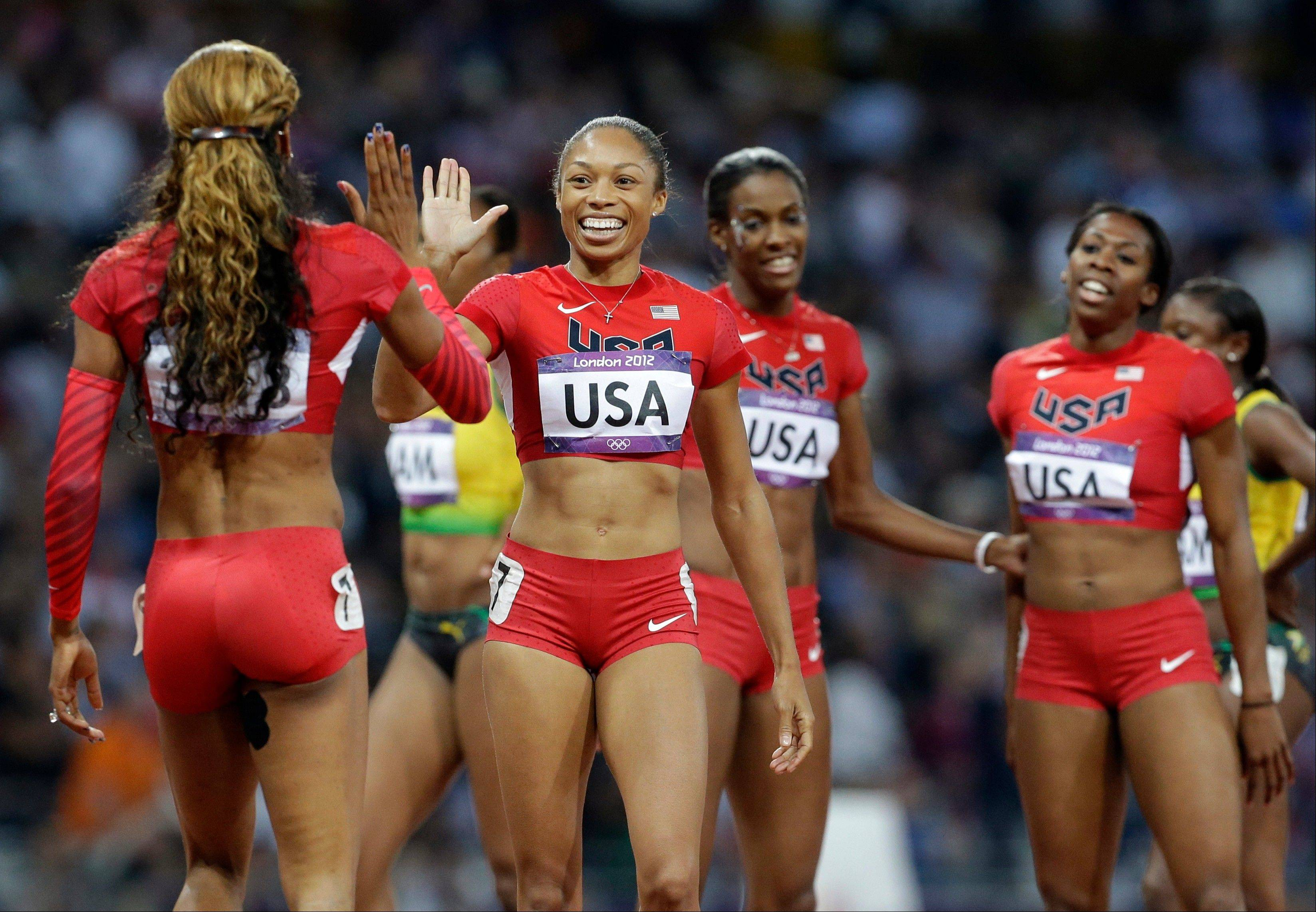 United States' Sanya Richards-Ross, left, celebrates with teammate United States' Allyson Felix, second left, with teammates Francena McCorory, right, and Deedee Trotter after their gold medal win in the women's 4 x 400-meter relay during the athletics in the Olympic Stadium at the 2012 Summer Olympics, London, Saturday, Aug. 11, 2012.