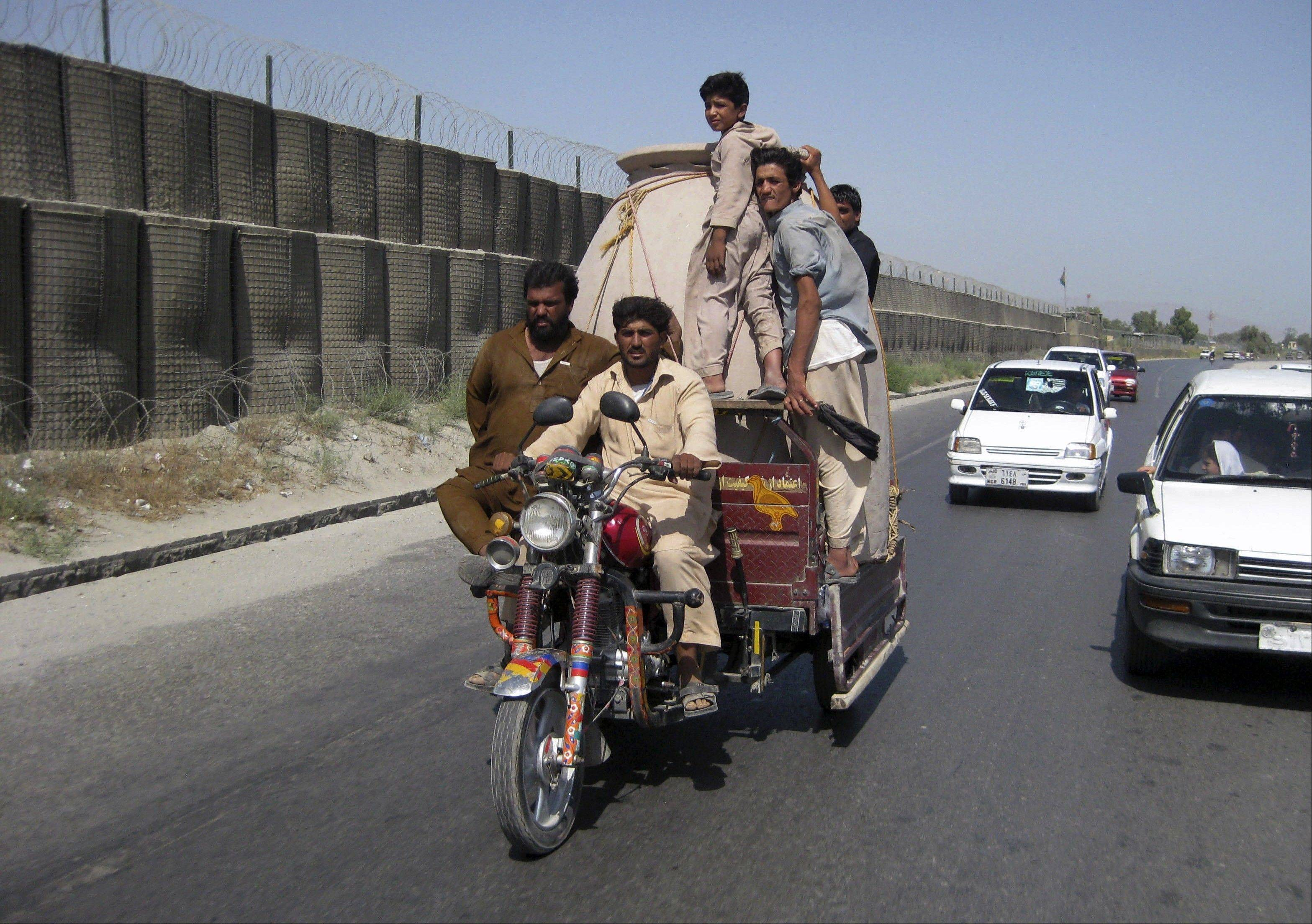 Afghans travel in a motorcycle cart Saturday while transporting a traditional tandoor oven in Jalalabad, east of Kabul, Afghanistan.
