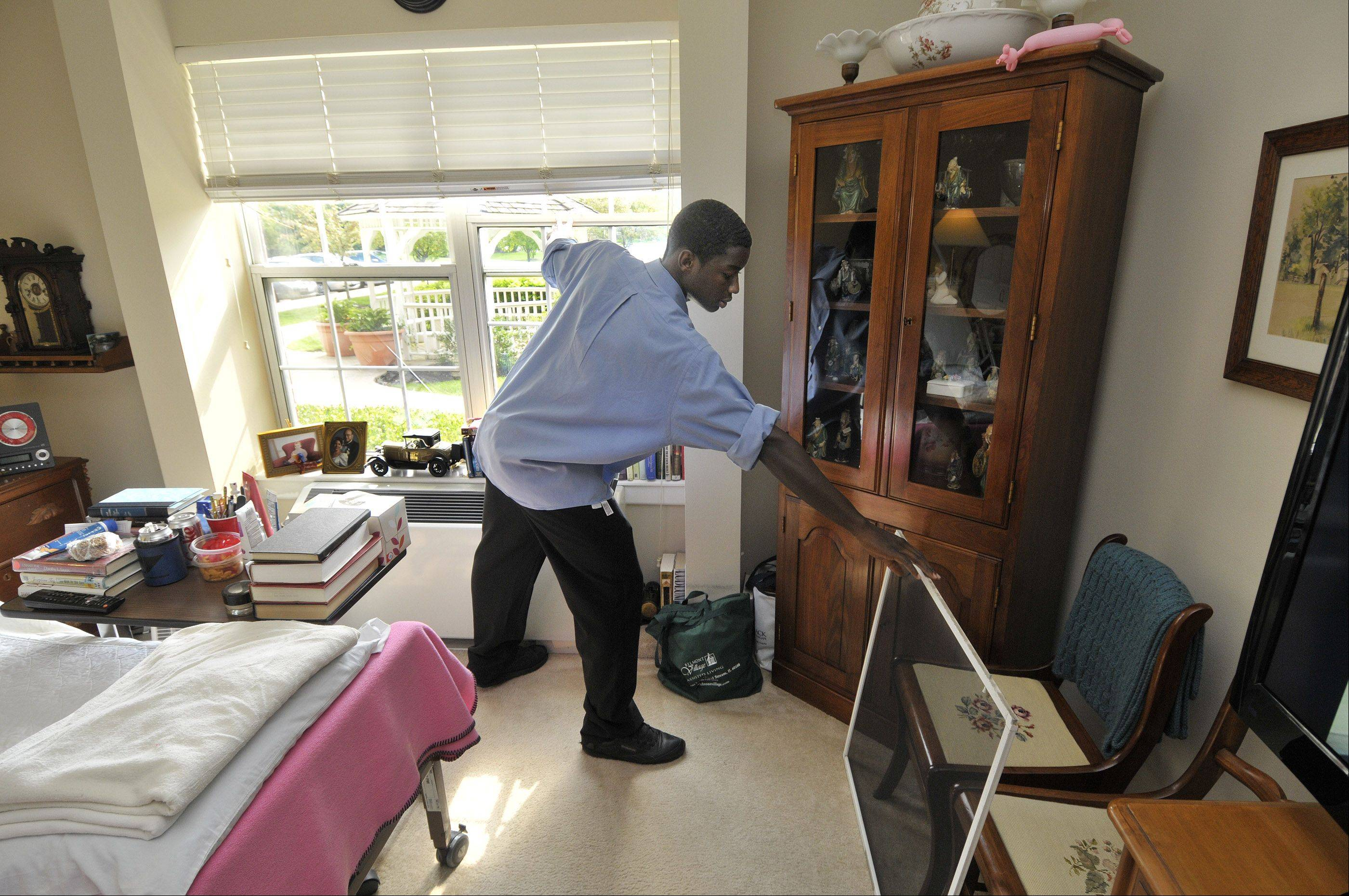 "Xavier Da'Shawn Brown replaces the screens in a resident's room after cleaning them at Belmont Village in Carol Stream. ""I think it'll help because it shows that I have a lot of skills and I could pertain to multiple jobs,"" Brown said of his work."