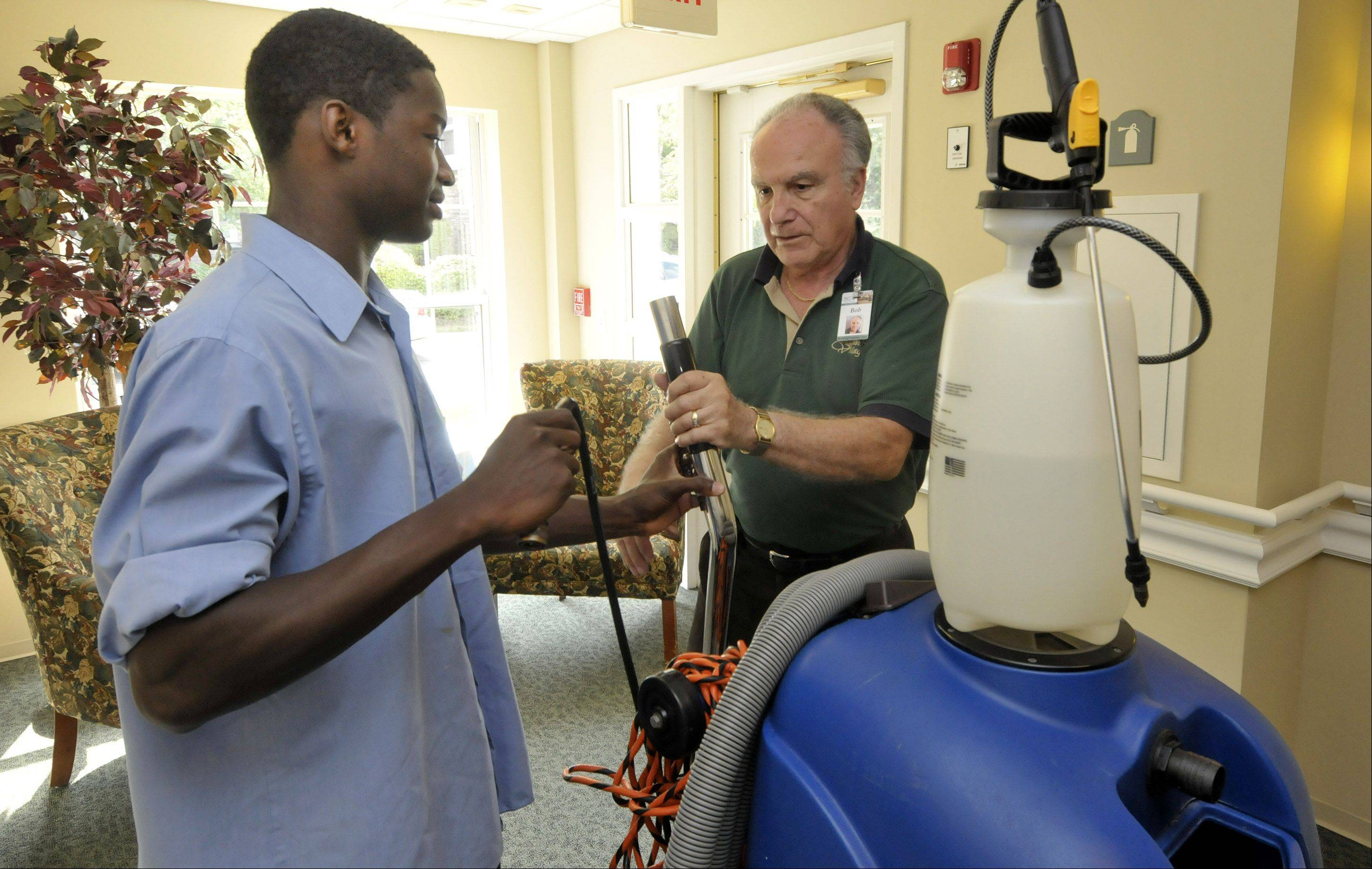 Xavier Da'Shawn Brown, left, receives job training and coaching with the SALT program to help him go on to college and succeed after high school. Here, he is assembling a carpet cleaner with Belmont Village's assistant building engineer Bob Shindle.