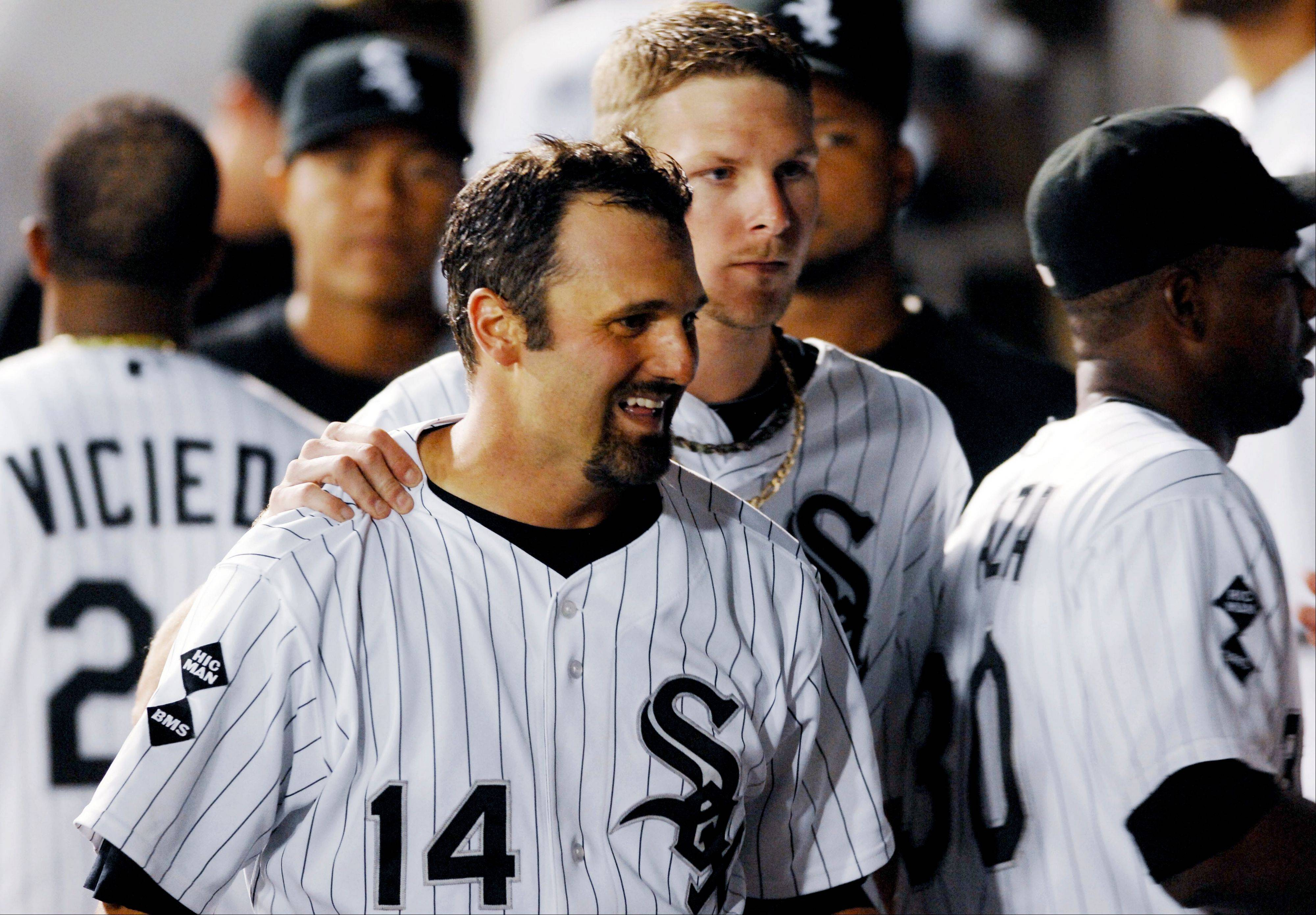 Chicago White Sox starting pitcher Chris Sale puts his hand on Paul Konerko's shoulder in the dugout after Konerko's home run in the seventh inning of a baseball game against the Kansas City Royals, Monday, Aug. 6, 2012, in Chicago. The White Sox won 4-2.