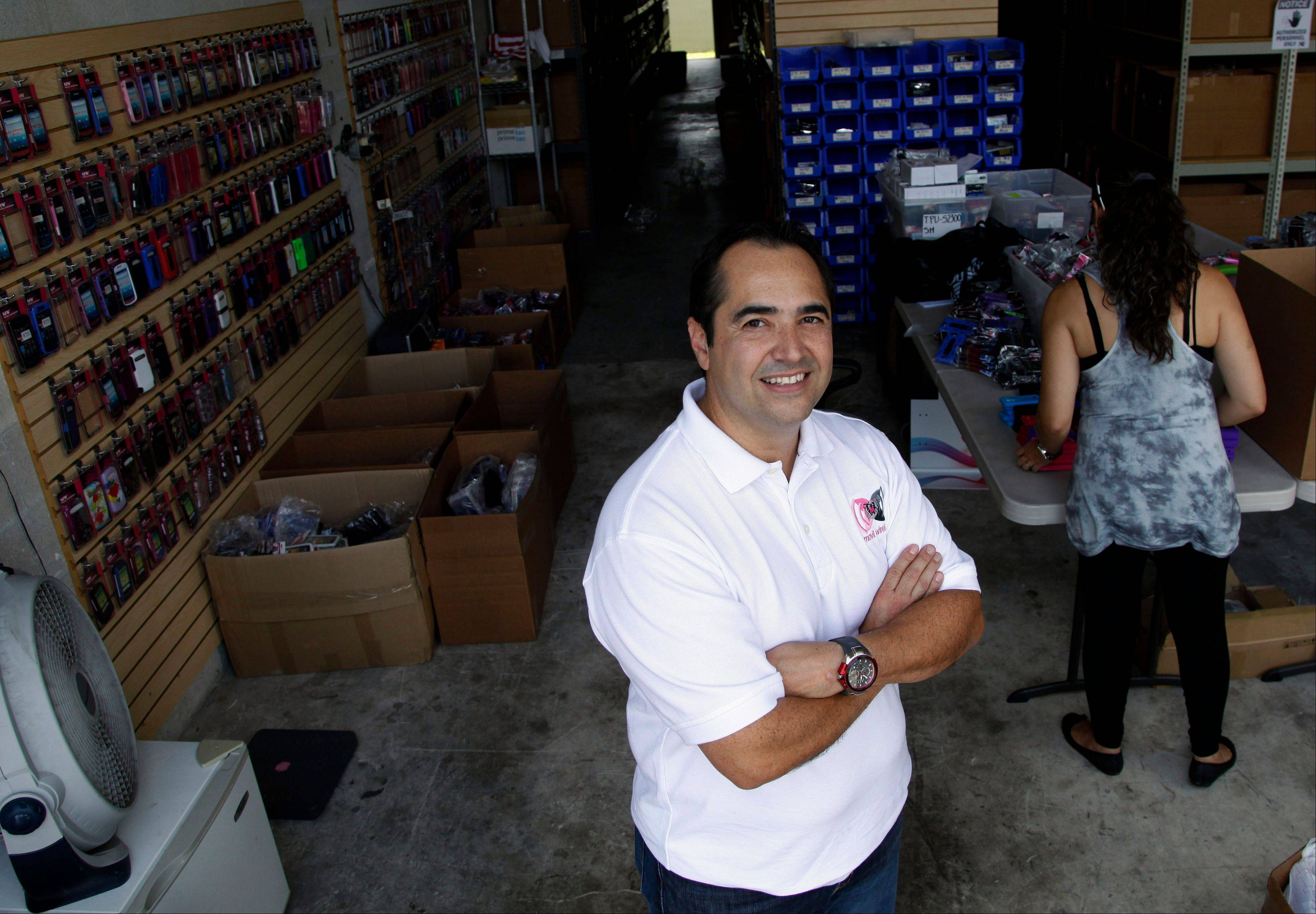 John Giraldo, vice president of Movil Wireless, stands in his warehouse, in Doral, Fla. Through a friend, Giraldo and his wife heard about the OUR Microlending program. His wife received five loans for more than $9,000 to expand inventory and later to rent a larger office.