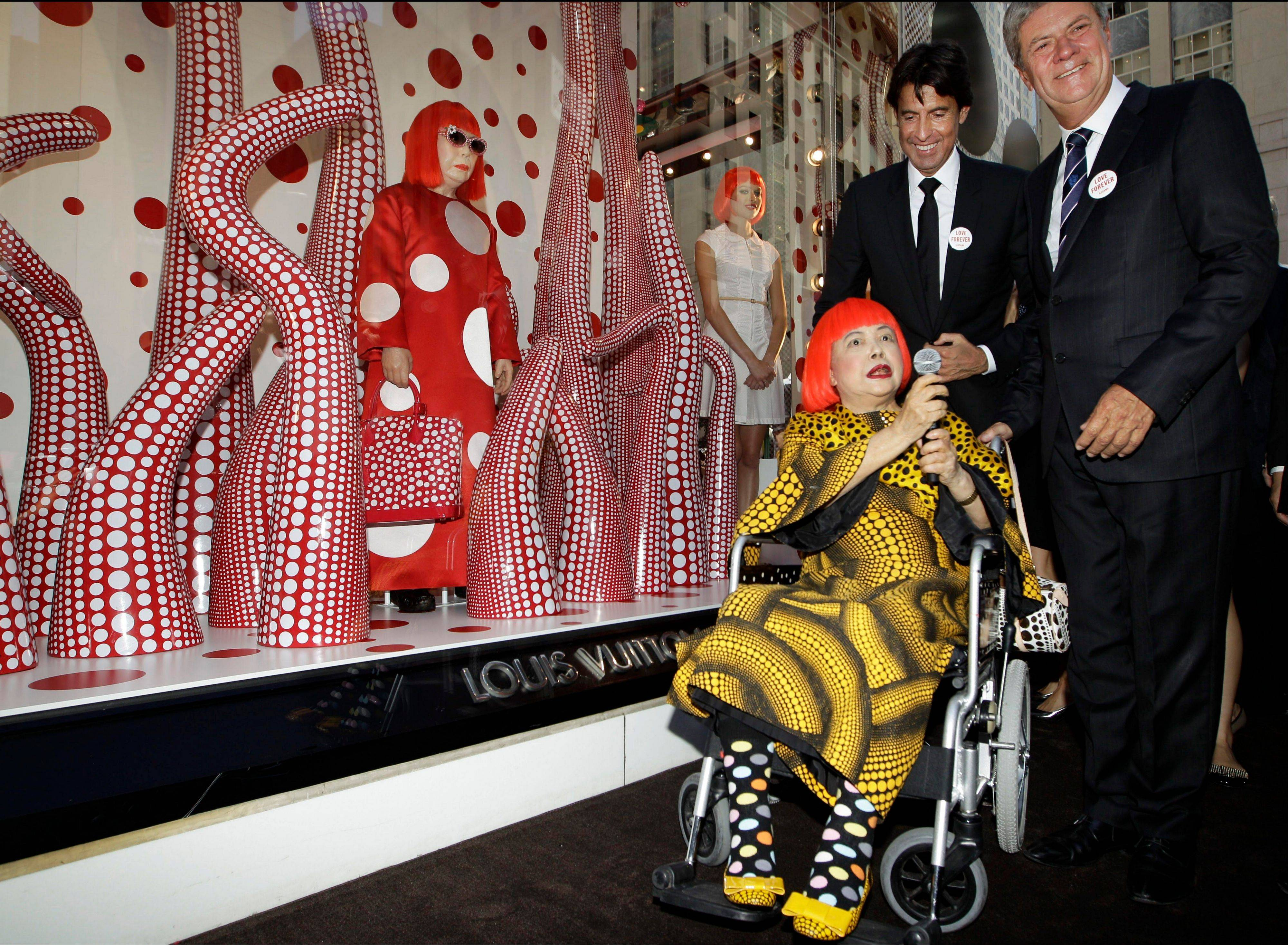 Japanese artist Yayoi Kusama in a red wig speaks on July 10 with Louis Vuitton's second in command, Jordi Konstans, left, and CEO Yves Carcelle, right, in front of the windows of Vuitton's flagship store for the unveiling of a new collaborative collection by Vuitton creative designer Marc Jacobs and Kusama in New York. Kusama's signature splash of dots has now arrived in the realm of fashion in a new collection from French luxury brand Louis Vuitton -- bags, sunglasses, shoes and coats. The latest Kusama collection is showcased at its boutiques around the world, including New York, Paris, Tokyo and Singapore, sometimes with replica dolls of Kusama.