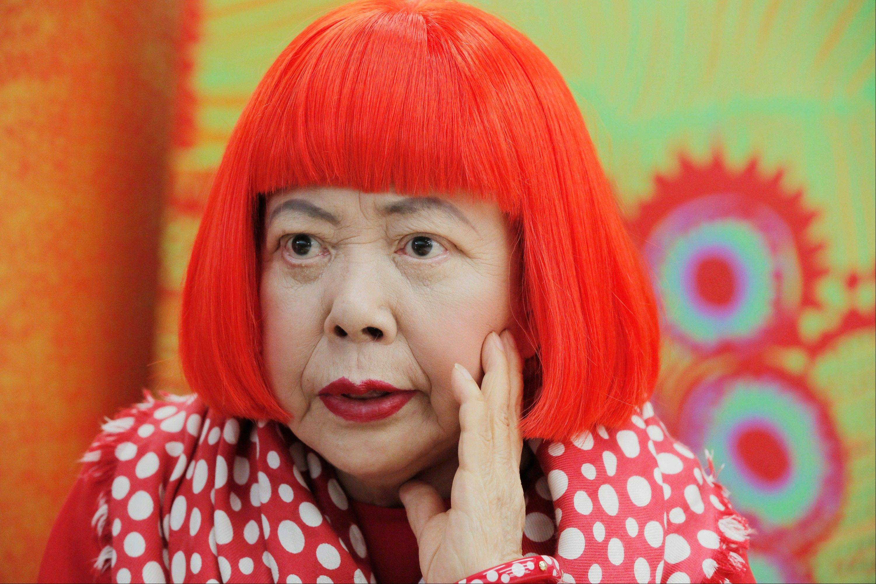 Japanese avant-garde artist Yayoi Kusama, wearing a bright red wig and a Louis Vuitton polka dot scarf, speaks during an interview at her studio in Tokyo on Aug. 1. Kusama's signature splash of dots has now arrived in the realm of fashion in a new collection from French luxury brand Louis Vuitton -- bags, sunglasses, shoes and coats. The latest Kusama collection is showcased at its boutiques around the world, including New York, Paris, Tokyo and Singapore, sometimes with replica dolls of Kusama.