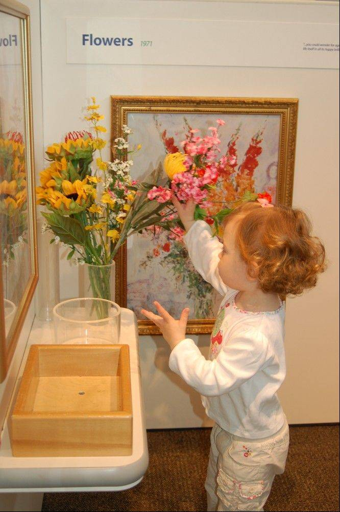 "A young girl creates a flower arrangement as part of the ""Chagall for Children"" exhibit at the Kohl Children's Museum in Glenview."