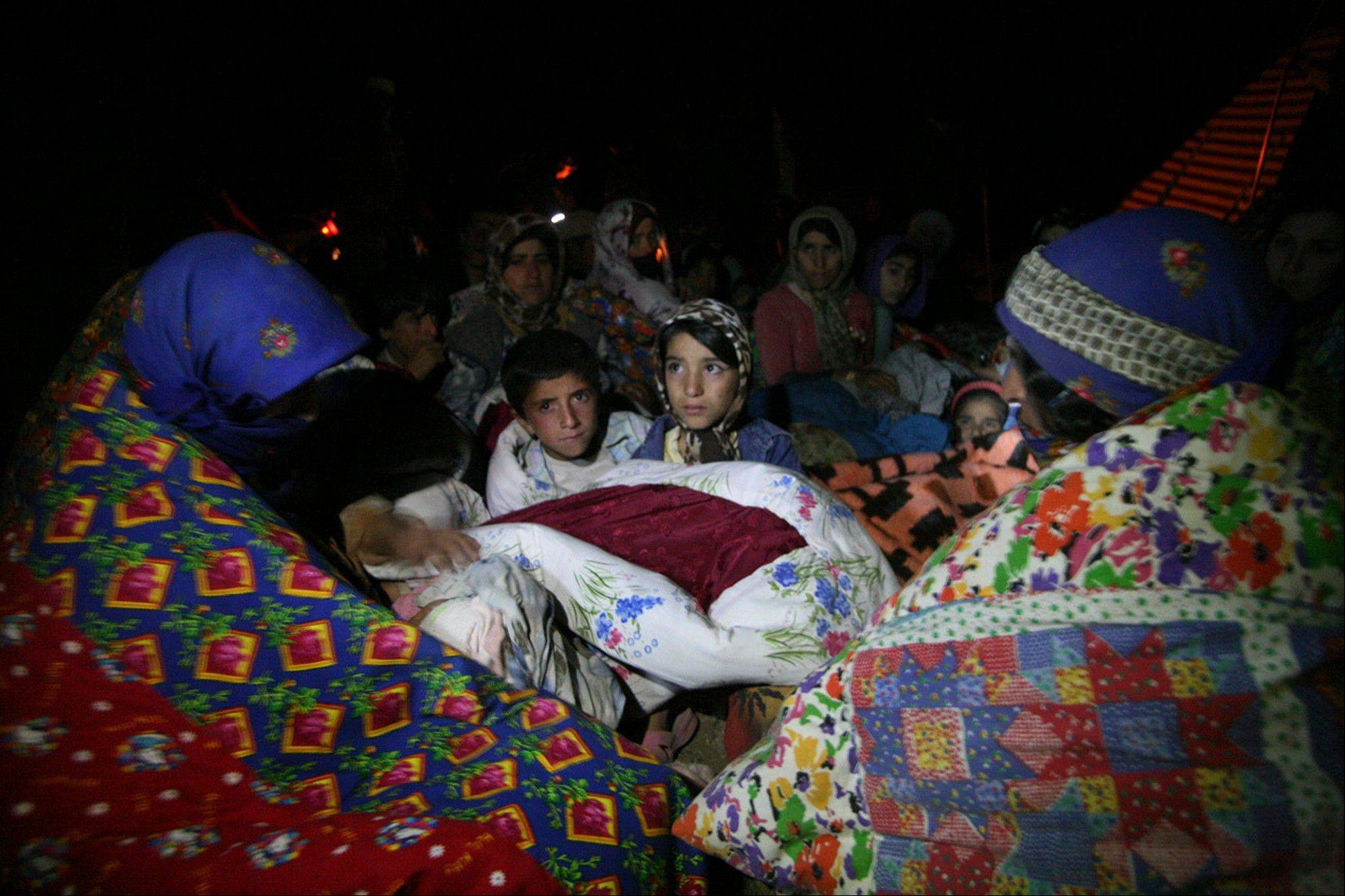 Residents spend the night outside their homes Saturday after an earthquake in the city of Varzaqan in northwestern Iran.
