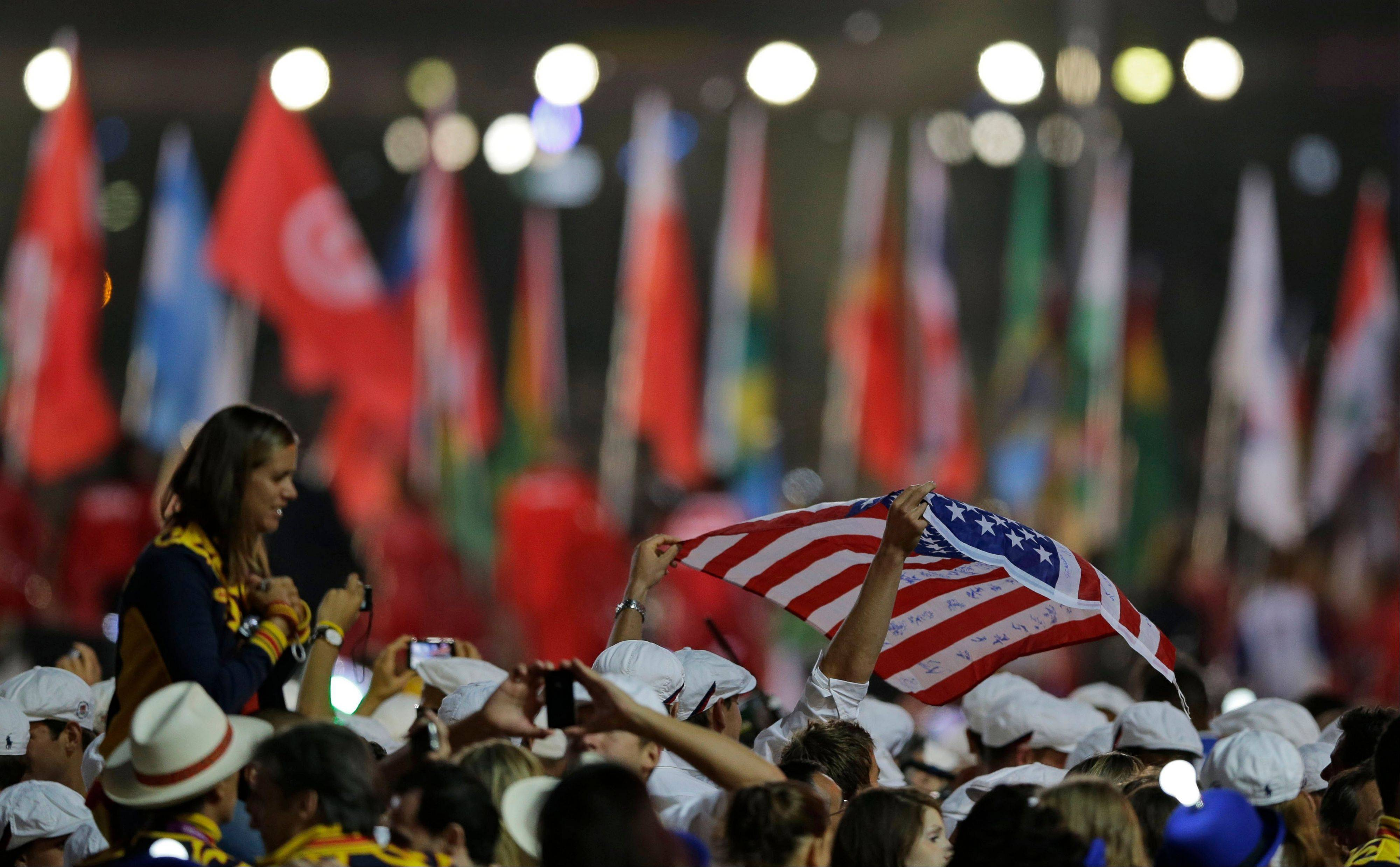 An athlete holds the U.S. flag as he enters the stadium with others during the Closing Ceremony at the 2012 Summer Olympics.