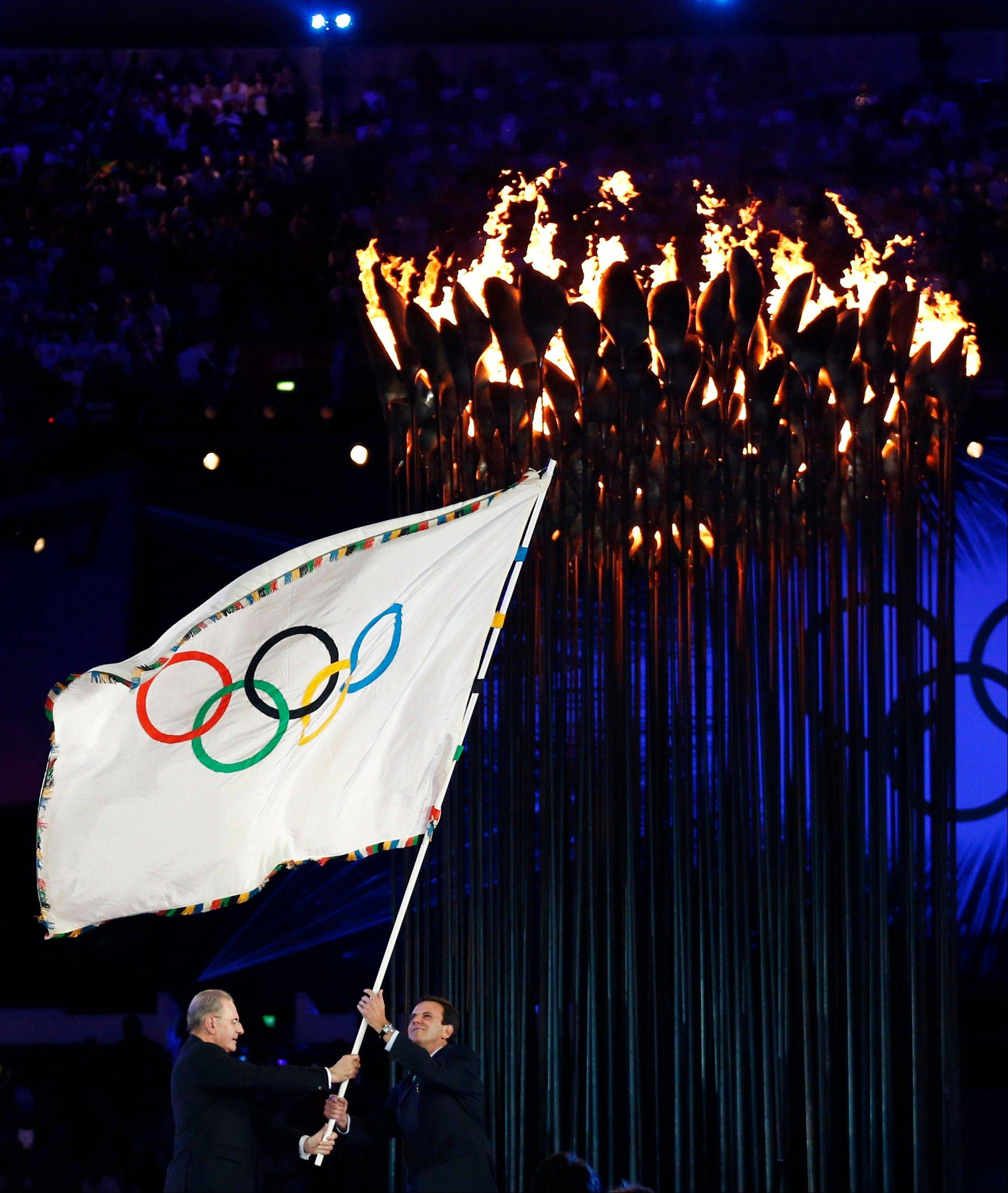 President of the International Olympic Committee Jacques Rogge, left, hands the Olympic flag to Rio de Janeiro's mayor Eduardo Paes during the Closing Ceremony at the 2012 Summer Olympics.