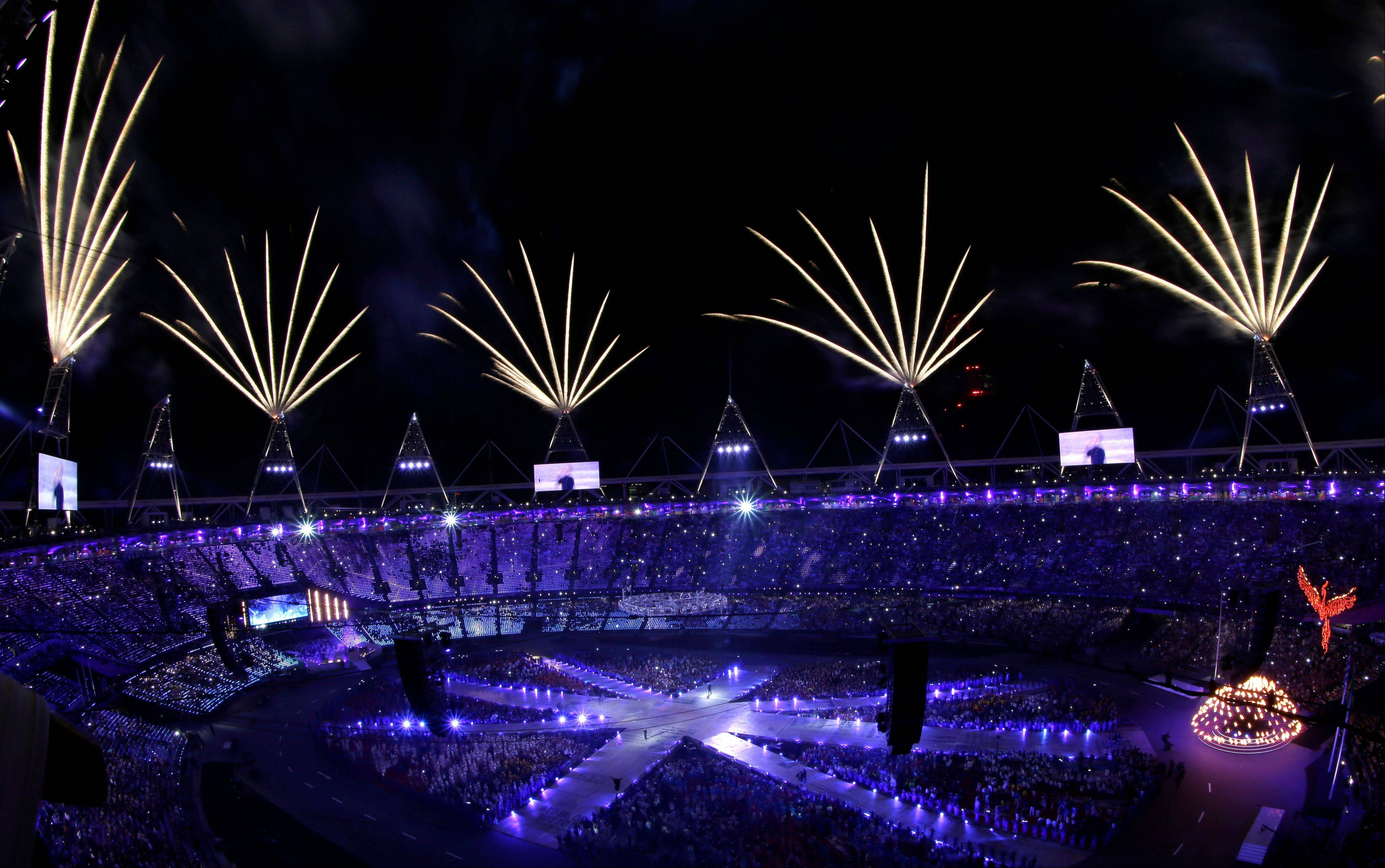Fireworks soar over the Olympic Stadium as the Olympic flame is lowered during the Closing Ceremony at the 2012 Summer Olympics.