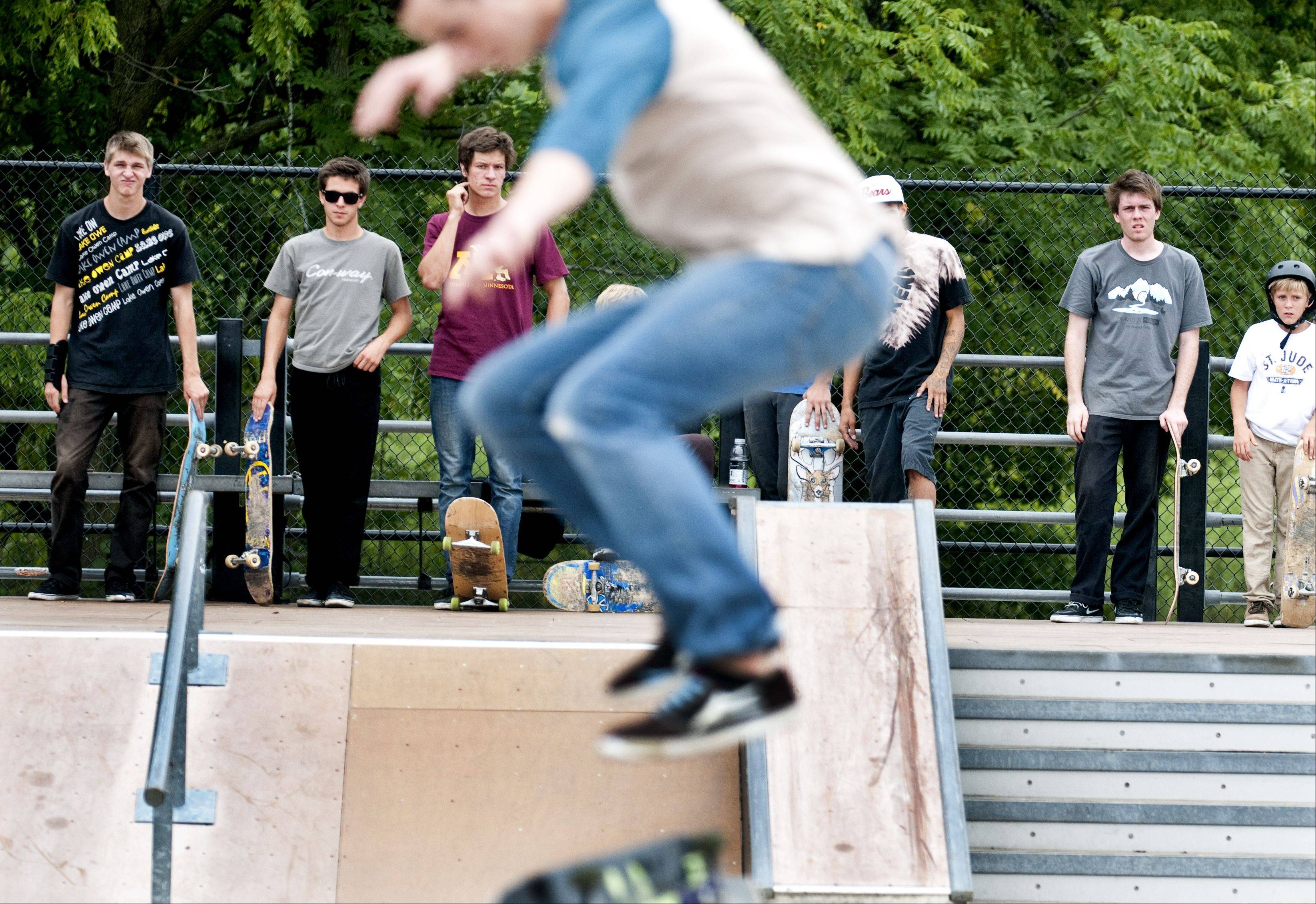 Skaters watch the best trick competition at a skateboard contest hosted Sunday by the Geneva Park District at the South Street skate park. Competitors were split into groups based on skill.