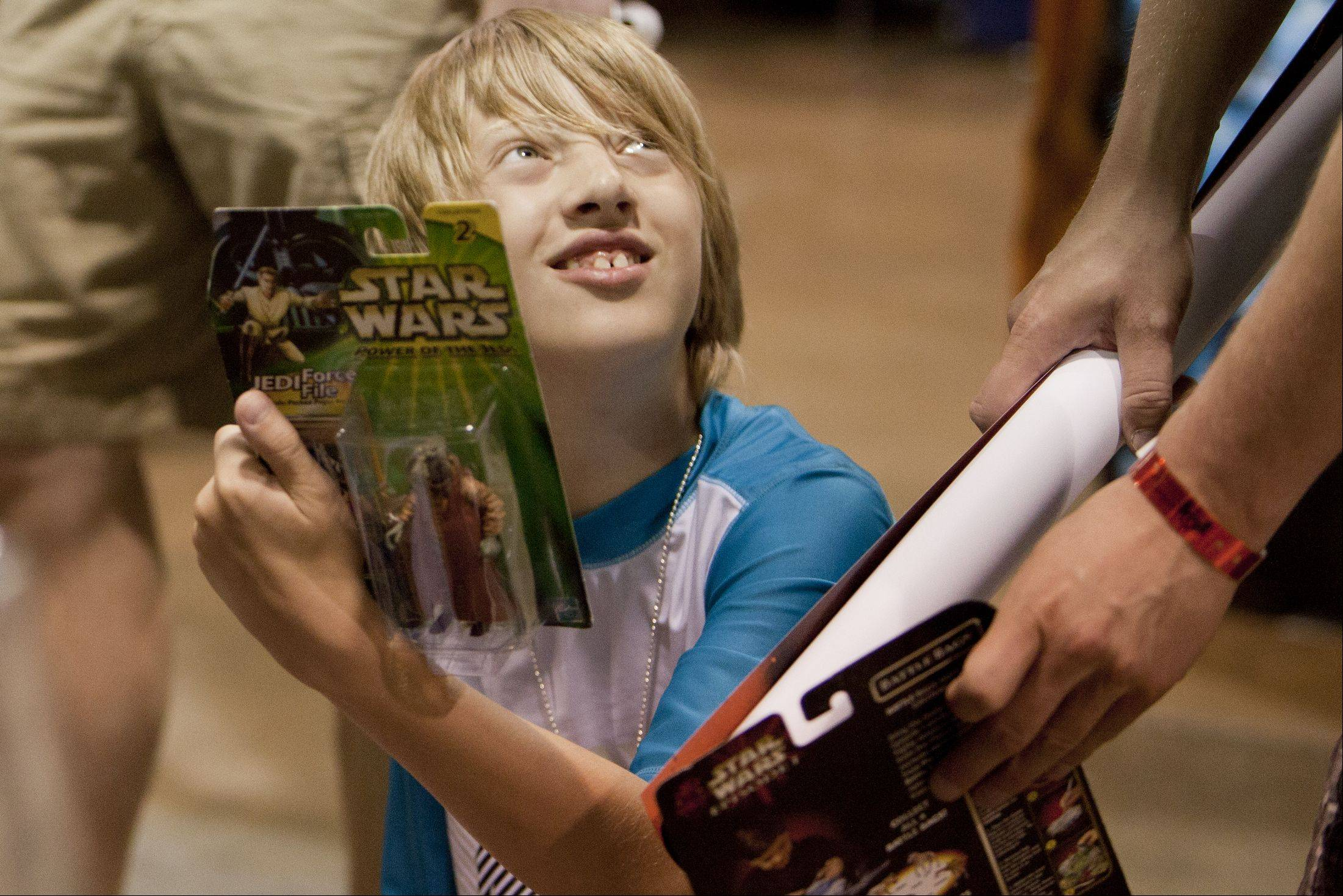 "13-year-old Robert Anderson of Kenosha, Wis. shows his father, Brian, a ""Power of the Jedi"" Star Wars toy during the annual Wizard World Chicago Comic Con at the Donald E. Stephens Convention Center in Rosemont."