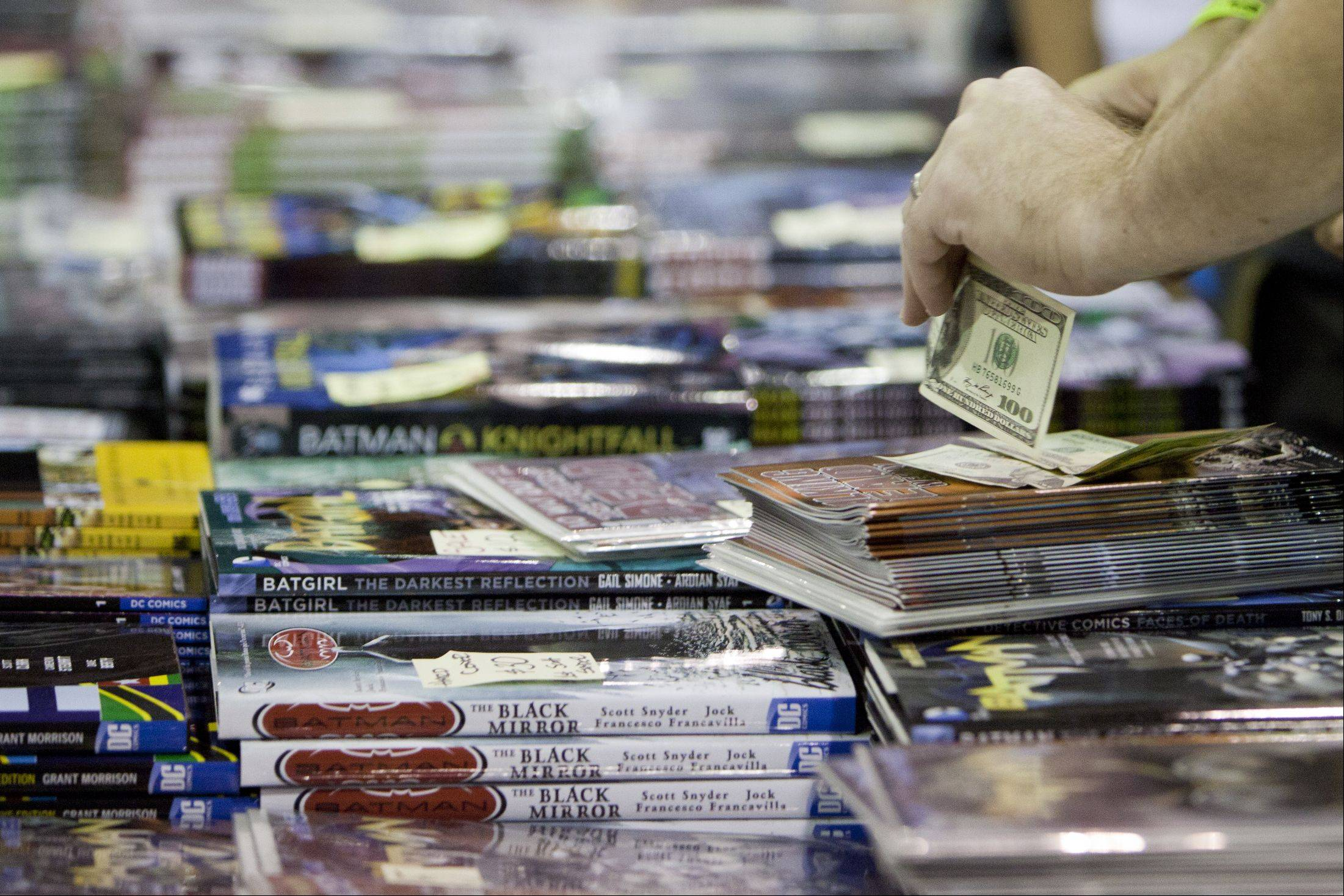 A Comic Con attendee hands over a few hundred dollars for some collectible DC Comics at the annual Wizard World Chicago Comic Con at the Donald E. Stephens Convention Center in Rosemont.
