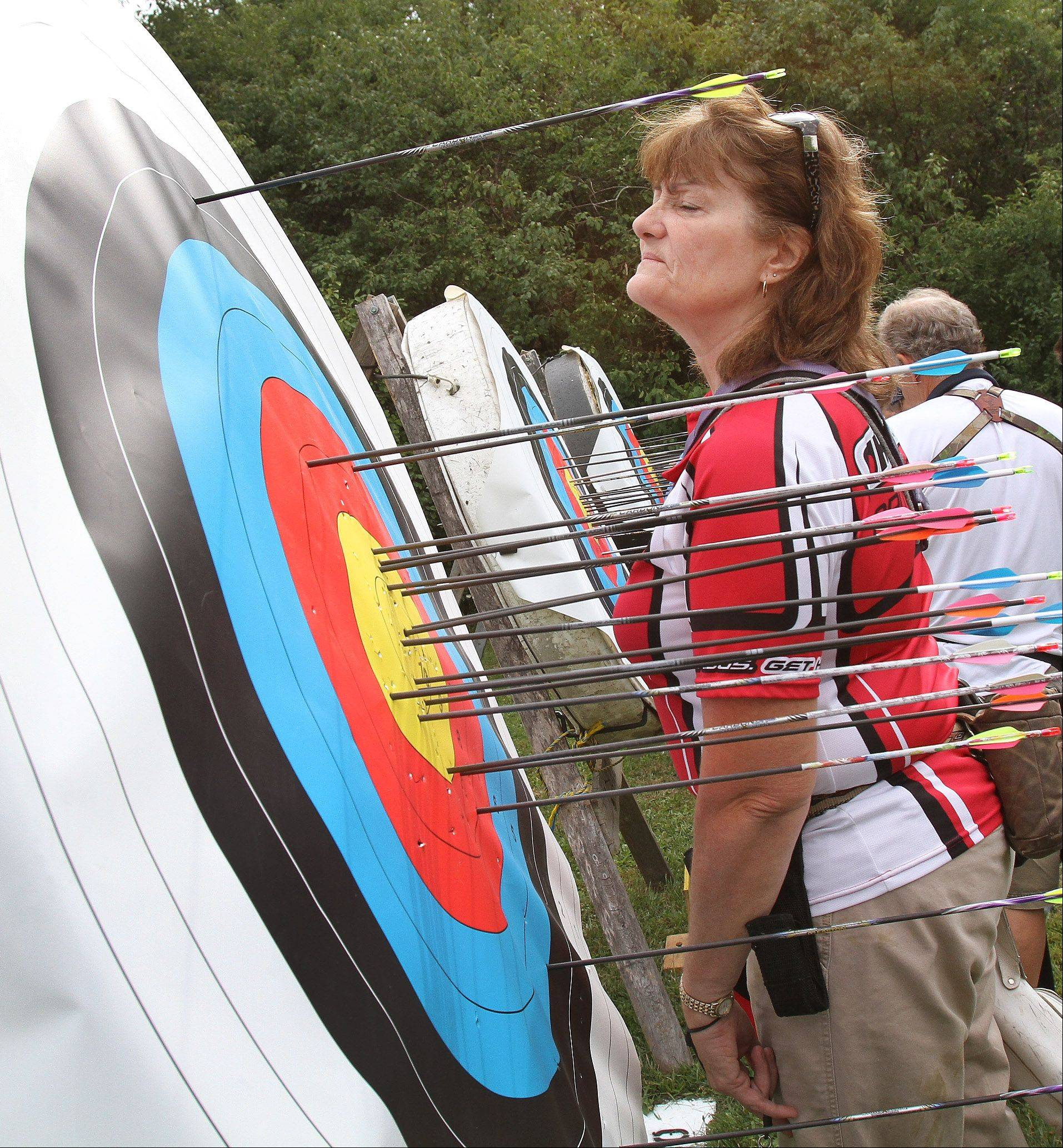 Nancy Zorn of Warrenville, competing in the compound bow division, checks a score during the Illinois Target Archery Association's annual Outdoor State Championship at Wheaton Rifle Club in West Chicago on Sunday.