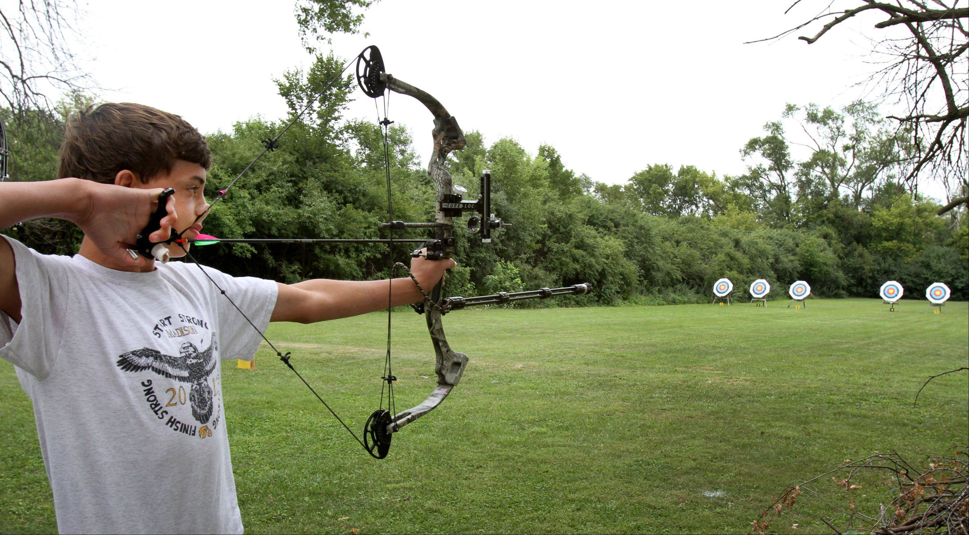 "Daniel Petro, 15, of Naperville, lines up his shot with a compound bow in the 900 metric round at a target of 60 meters, as he competes in the Illinois Target Archery Association's annual Outdoor State Championship at Wheaton Rifle Club in West Chicago on Sunday. ""This is a sport that is growing in popularity, especially with kids"", said Tom Havel, president of ITAA."