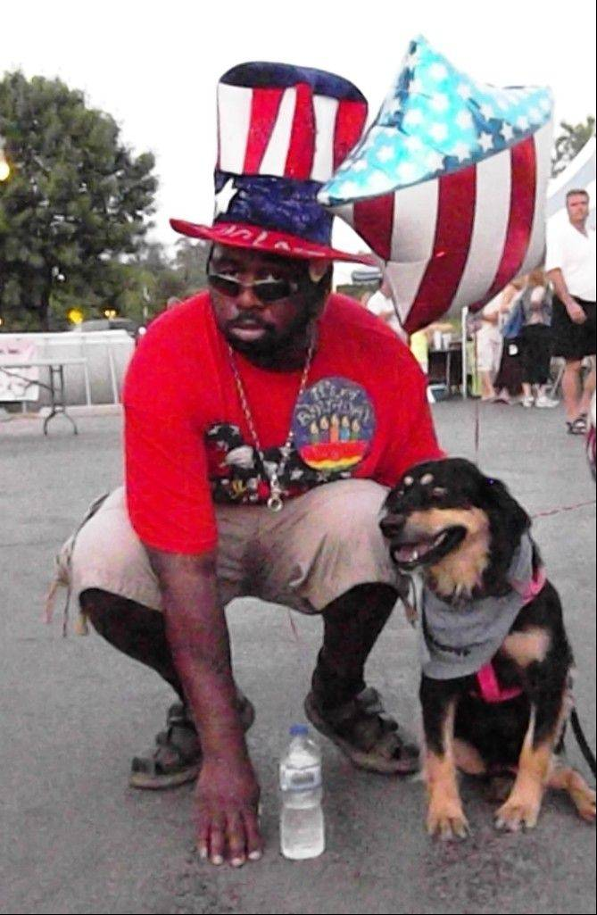 "During a Wisconsin festival last month, Winiom ""Noah"" Woods, a military veteran who had to relearn how to walk after he was shot in the head in Iraq, kneels to share a moment with Sadie, a dog who is undergoing therapy in Grayslake and elsewhere after being shot in the head."