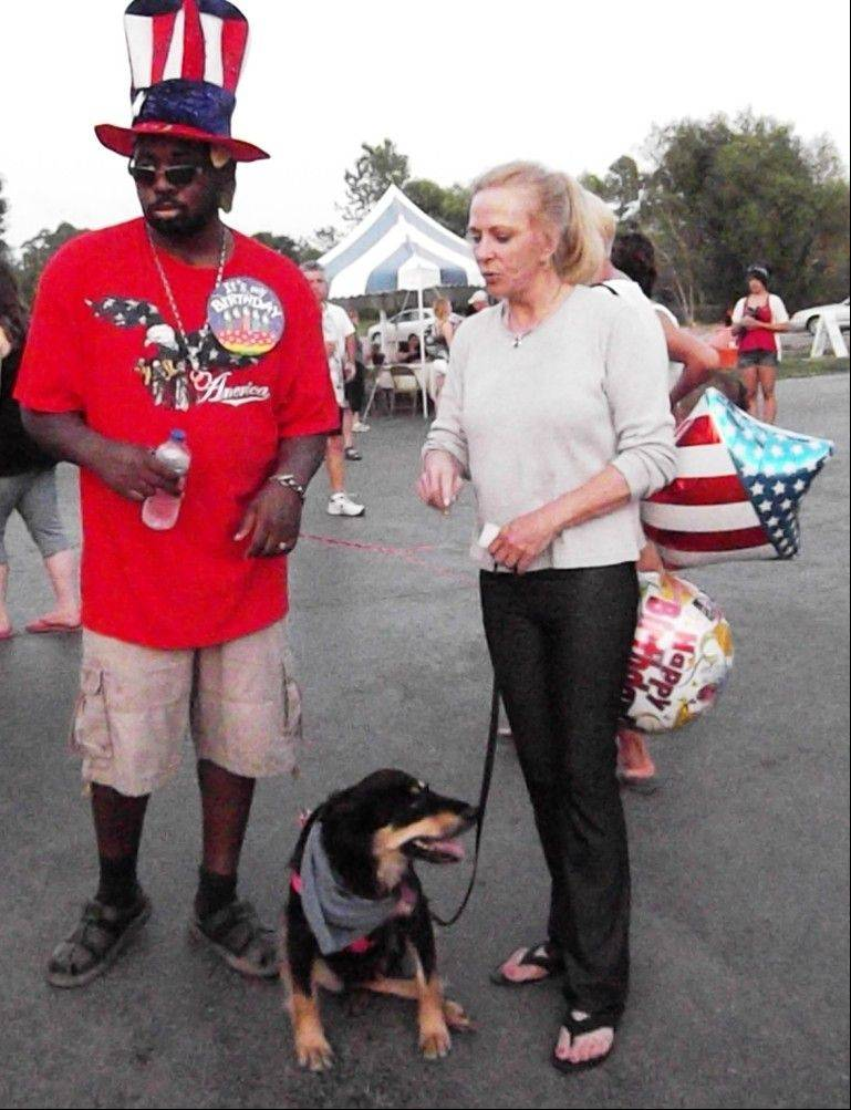 "During a July festival in Wisconsin, Winiom ""Noah"" Woods, left, a military veteran who had to relearn how to walk after he was shot in the head in Iraq, shares a moment with Joal Derse Dauer and her dog, Sadie, who is undergoing therapy in Grayslake and elsewhere after being shot in the head."