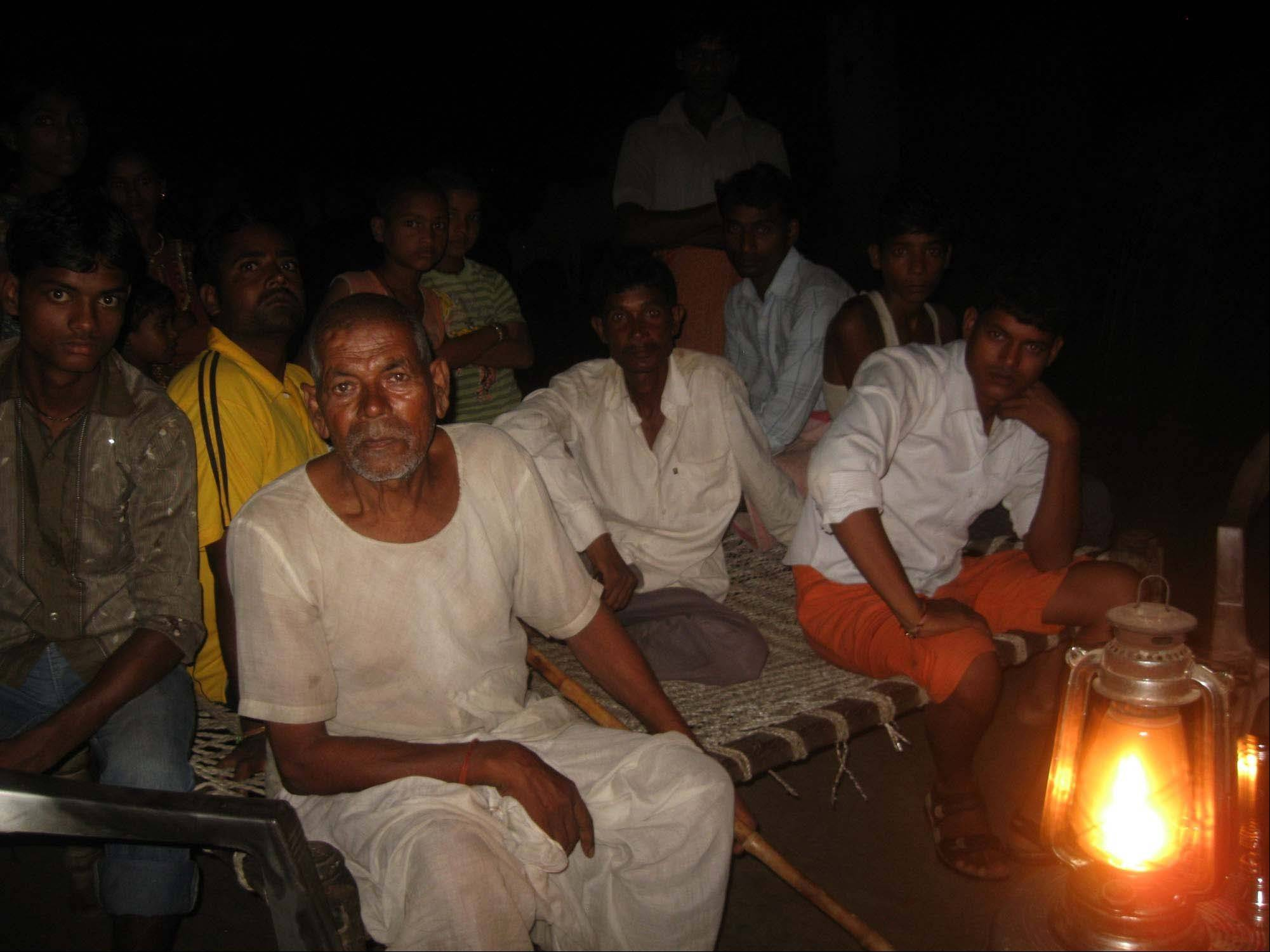 Raja Ram, 65, and others sit on a cot by a kerosene lantern in a riverside village called Kenwasia. The village, in the official files, has been given electricity, but only 30 homes out of 700 homes have electricity connections.
