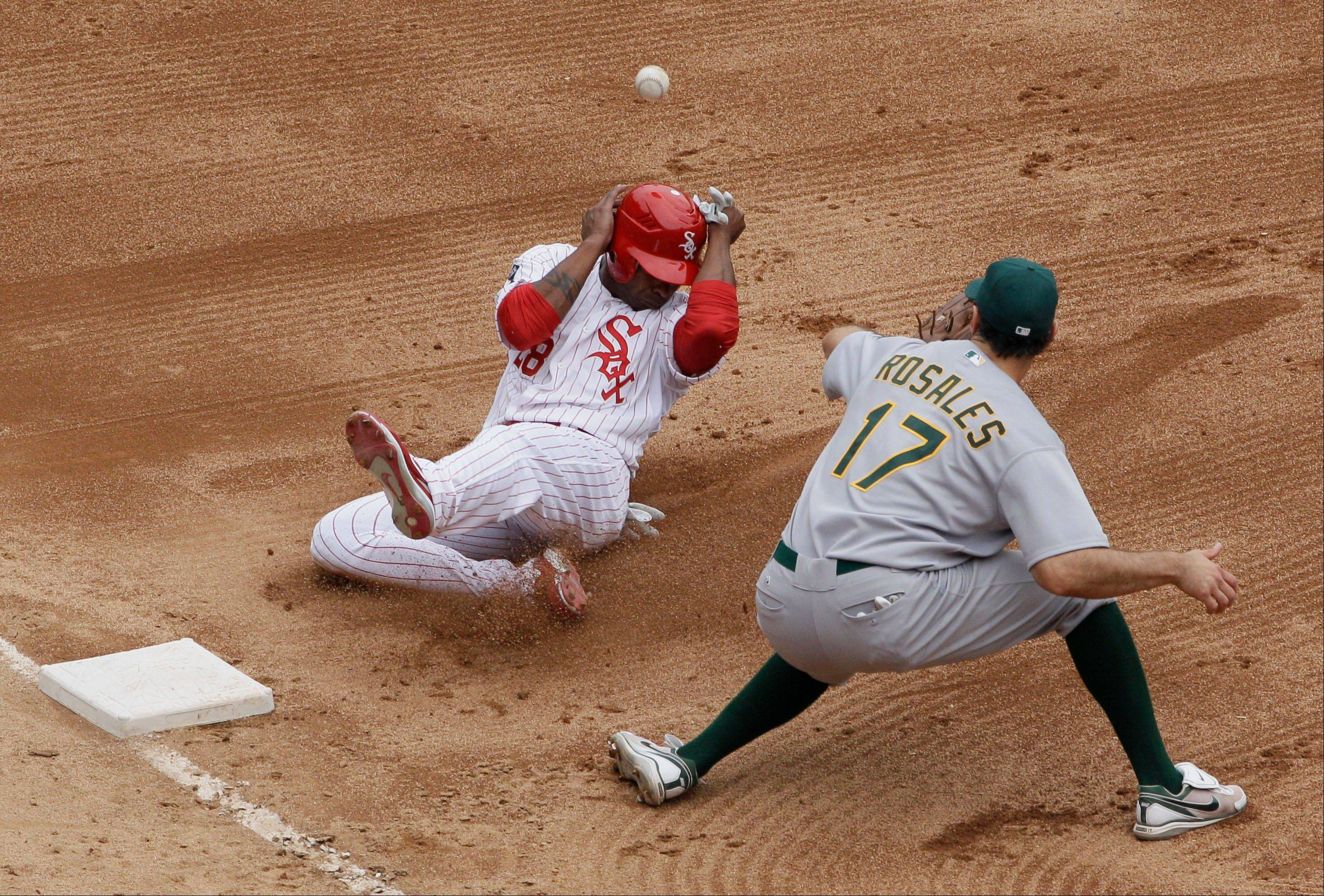 Dewayne Wise, left, is safe at third base as Oakland Athletics third baseman Adam Rosales waits for the ball during the sixth inning of a baseball game in Chicago, Sunday, Aug. 12, 2012.