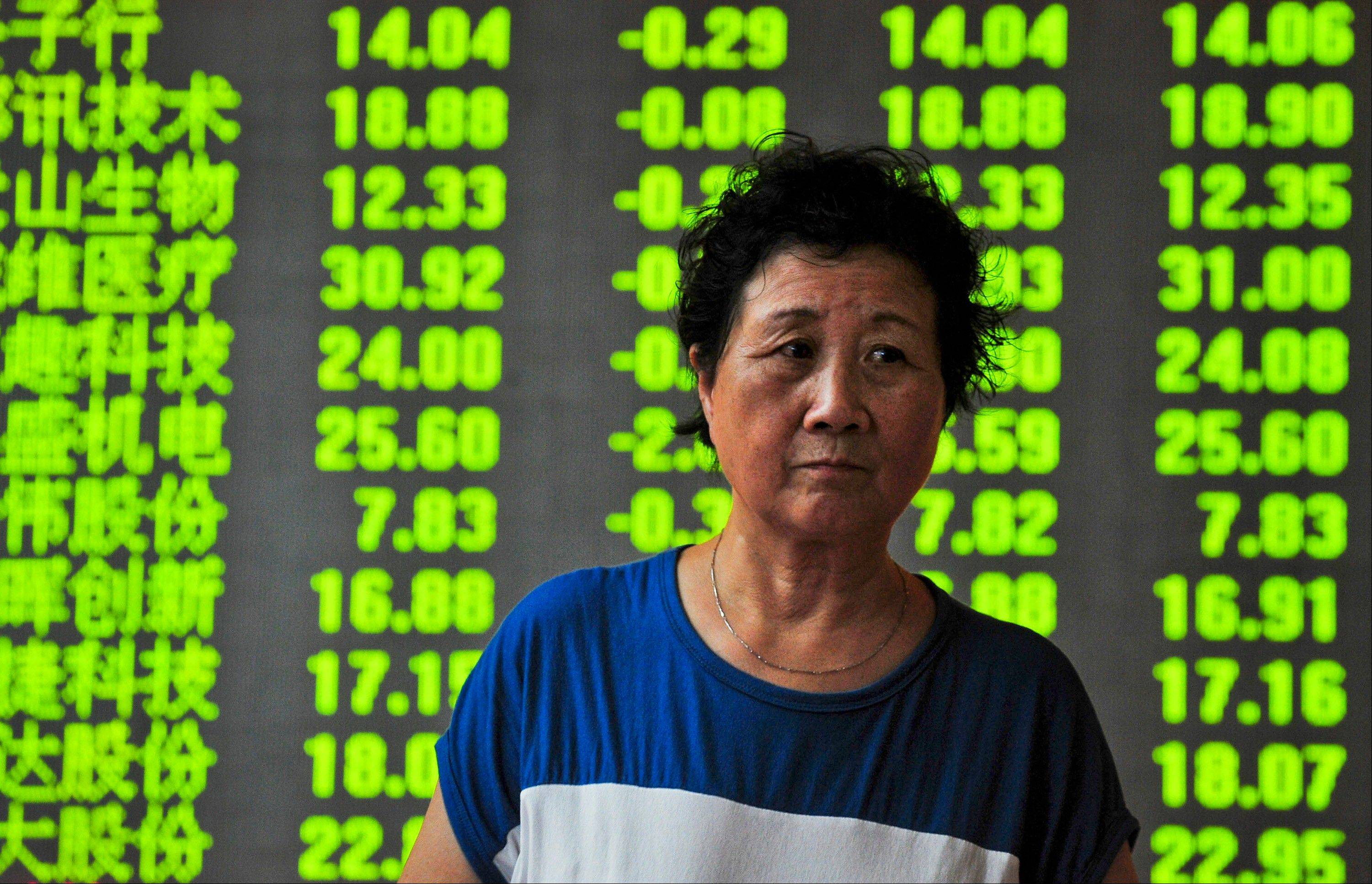 A woman walks past a screen showing the China Composite Stock Price Index at a brokerage house in Shenyang in northeast China�s Liaoning province Monday.