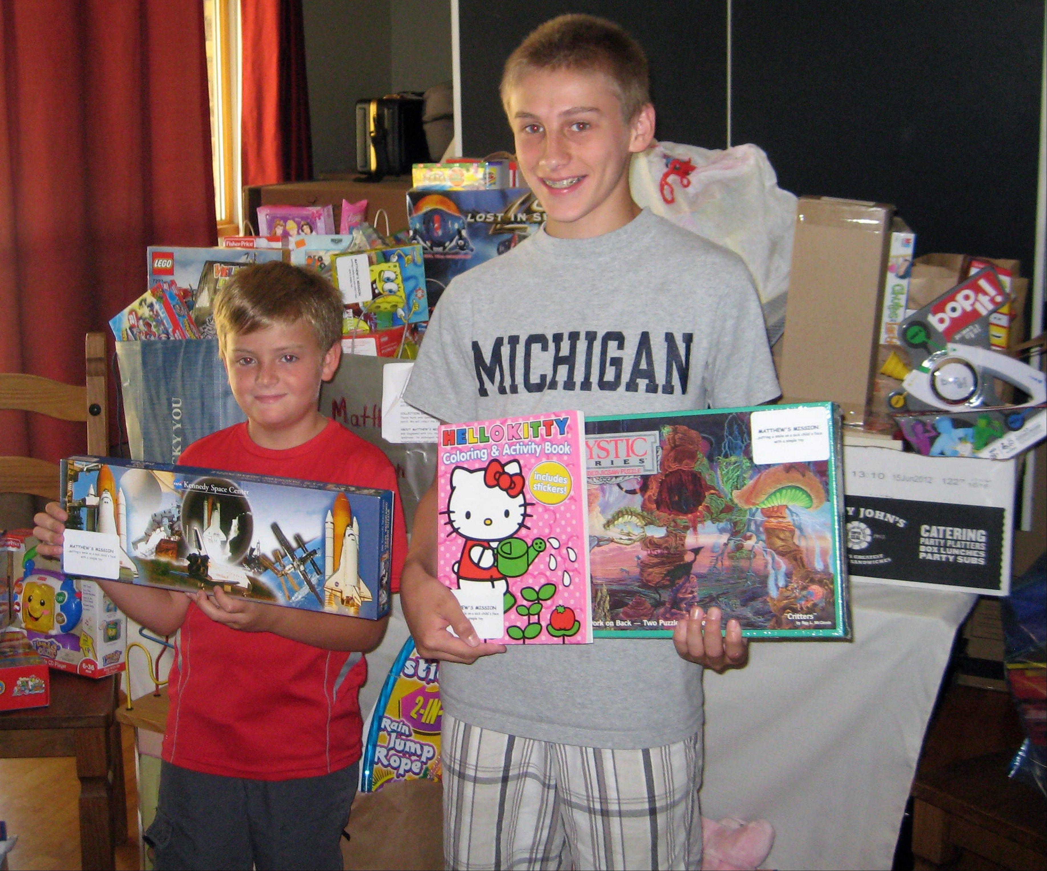 Blake Maley and Matthew Devine with some of the toys the drive collected.