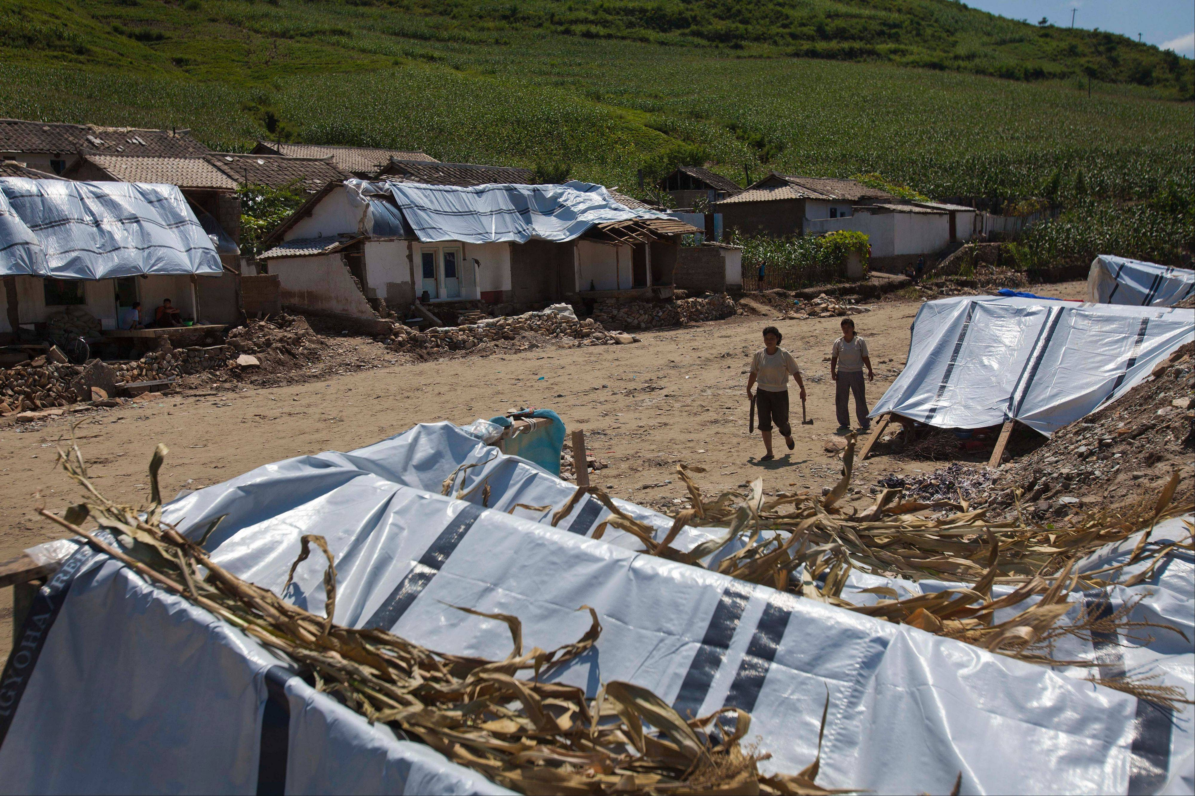 Displaced North Korean women, left homeless by July flooding, walk among temporary tents set up in their destroyed neighborhood in Ungok, North Korea, on Monday. Floods killed at least 169 North Koreans nationwide and destroyed tens of thousands of homes.