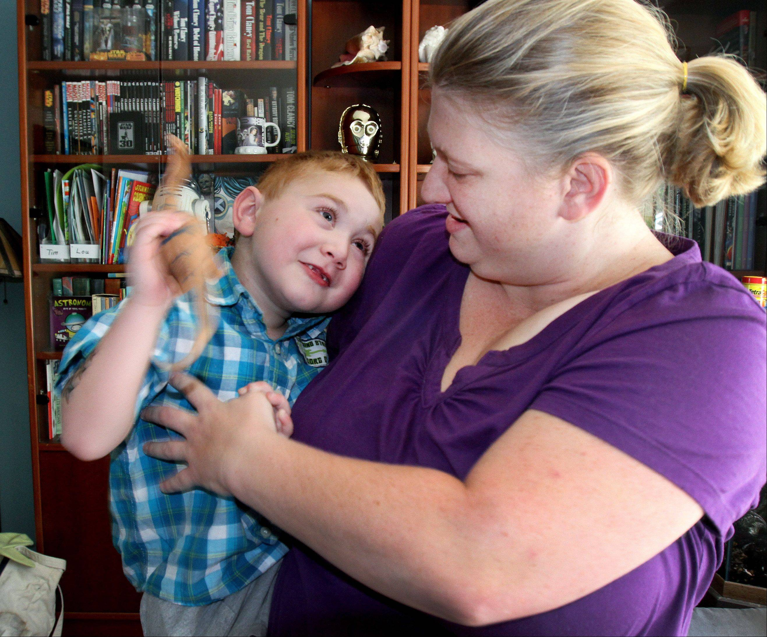 Christine Grobart, holds, son, Tim, 5, of Lombard, who is now back at home and active after a successful heart transplant.