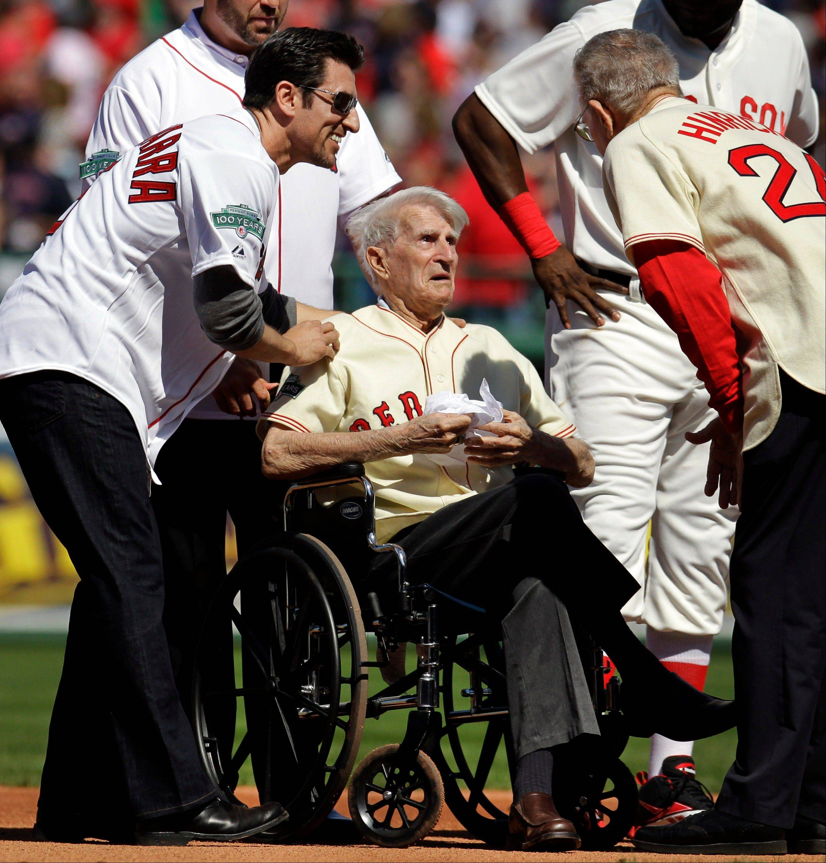 In this April 20, 2012, file photo, Boston Red Sox great Johnny Pesky, center, is greeted by former player Nomar Garciaparra, left, and others during a celebration of the 100th anniversary of the first regular-season baseball game at Fenway Park prior to the Red Sox taking on the New York Yankees in Boston. Pesky, who spent most of his 60-plus years in pro baseball with the Red Sox and was beloved by the team's fans, has died on Monday, Aug. 13, 2012, in Danvers, Mass. He was 92.