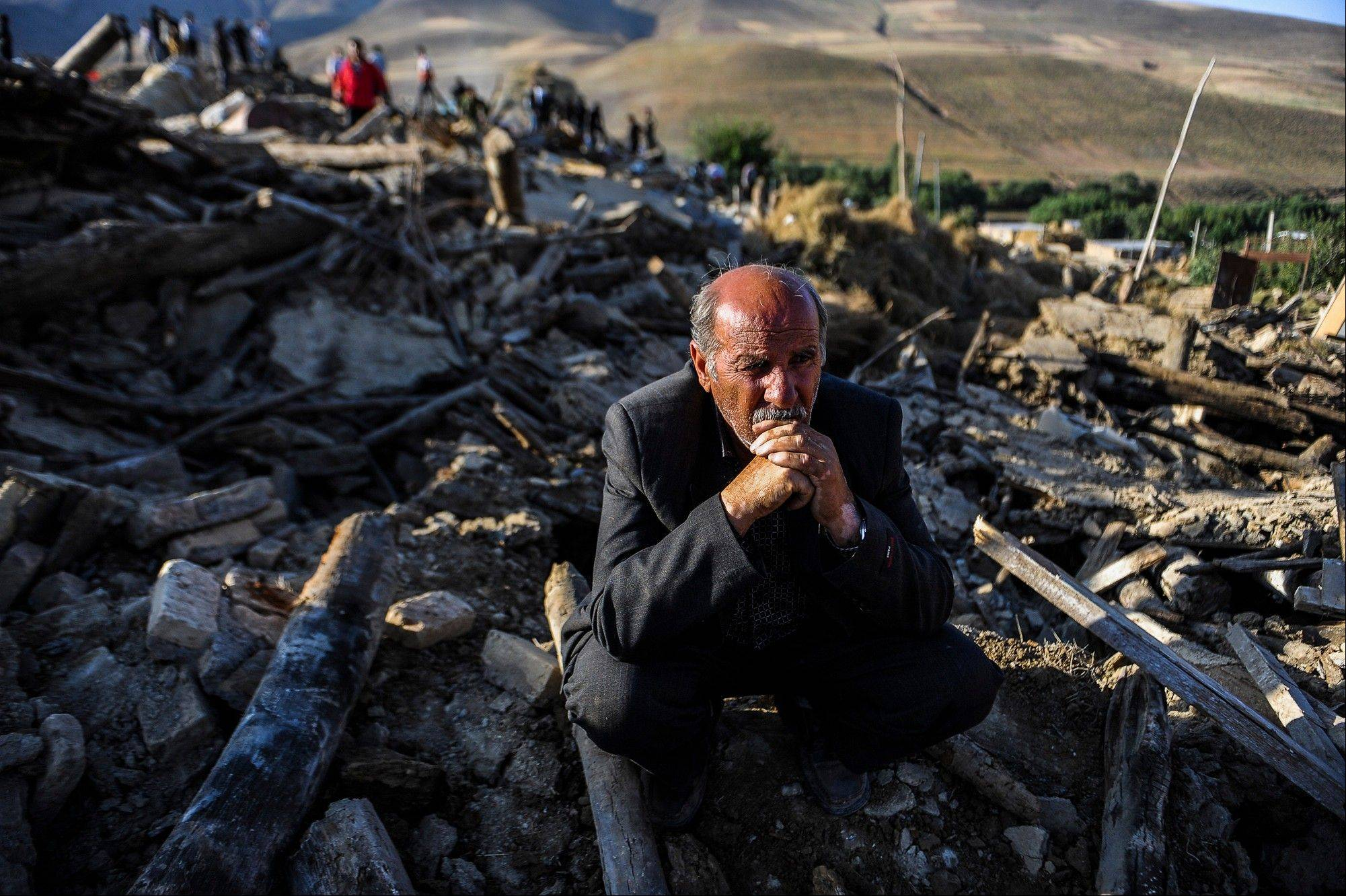 A victim of Saturday's earthquake sits on the ruins of buildings at the village of Bajebaj near the city of Varzaqan in northwestern Iran, Sunday. Twin earthquakes in Iran have killed at least 250 people and injured more than 2,000, Iranian state television said on Sunday.