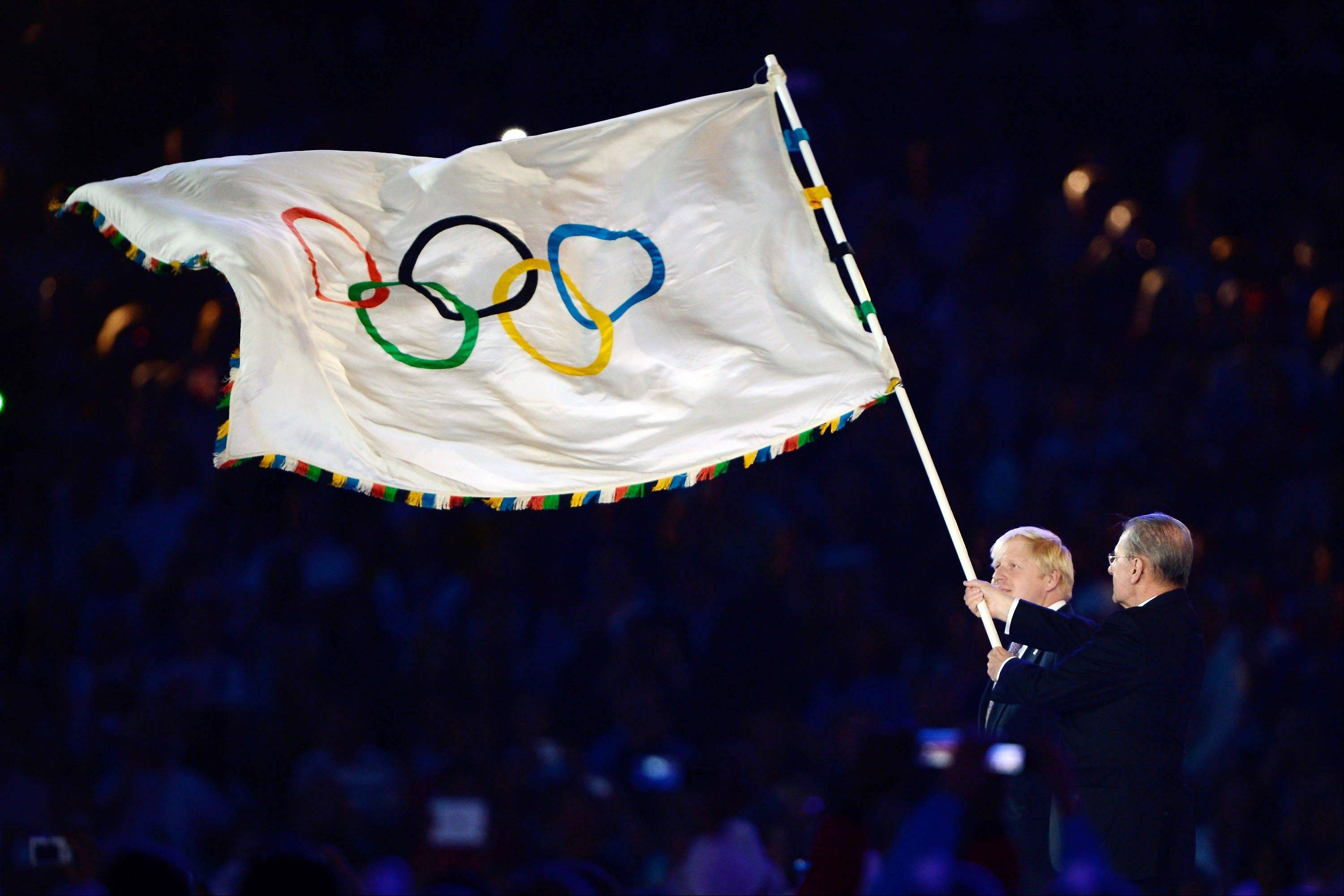 The Olympic flag is handed from London Mayor Boris Johnson, left, to the International Olympic Committee President Jacques Rogge during the closing ceremony of the 2012 Summer Olympics on Sunday in London.