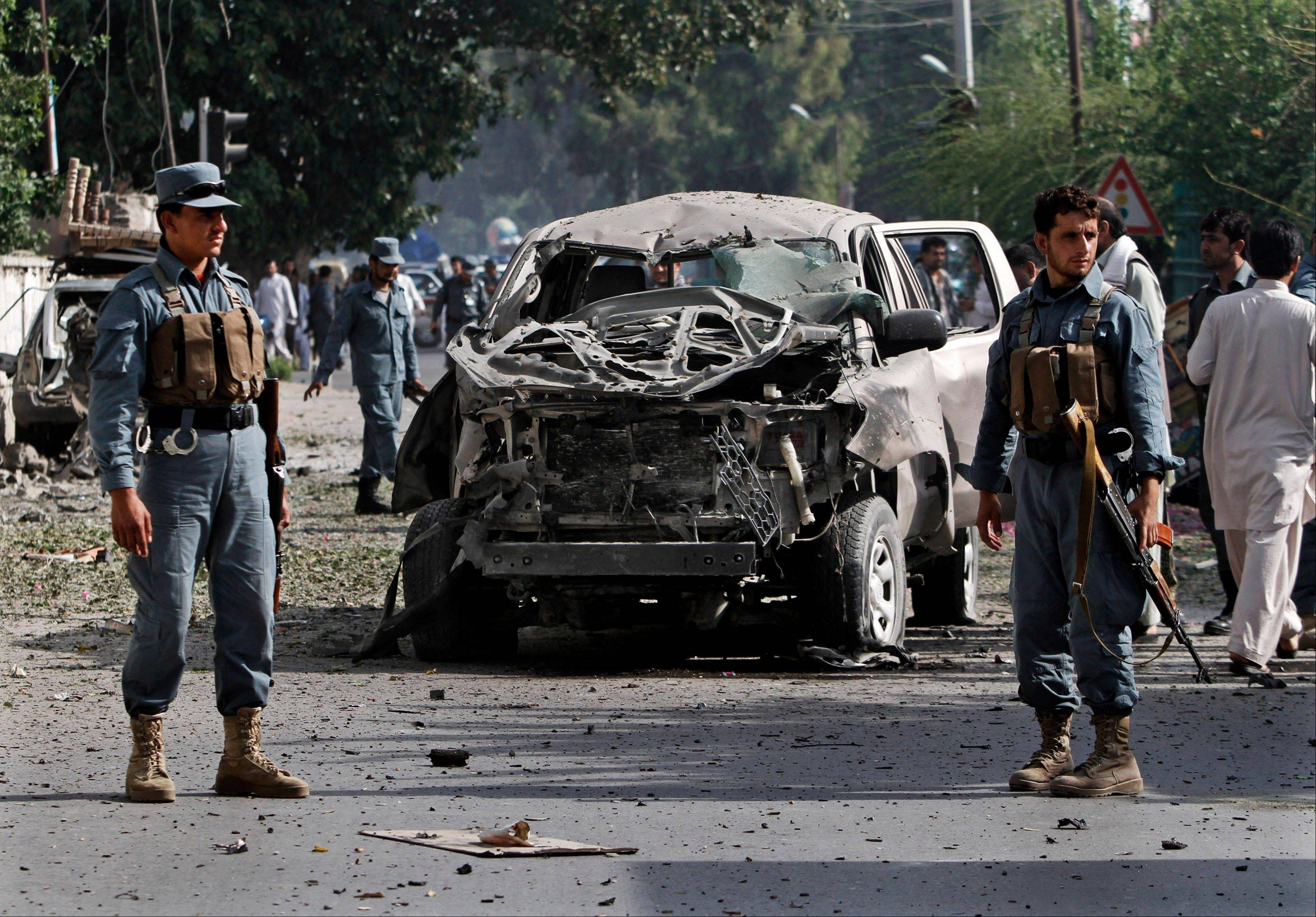 Afghan Police officers inspect the wreckage of vehicle after a bomb explosion in the city of Jalalabad east of Kabul, Afghanistan, Monday. At least five civilians were injured as a bomb targeting a government employees' bus went off Monday morning, a police source said.