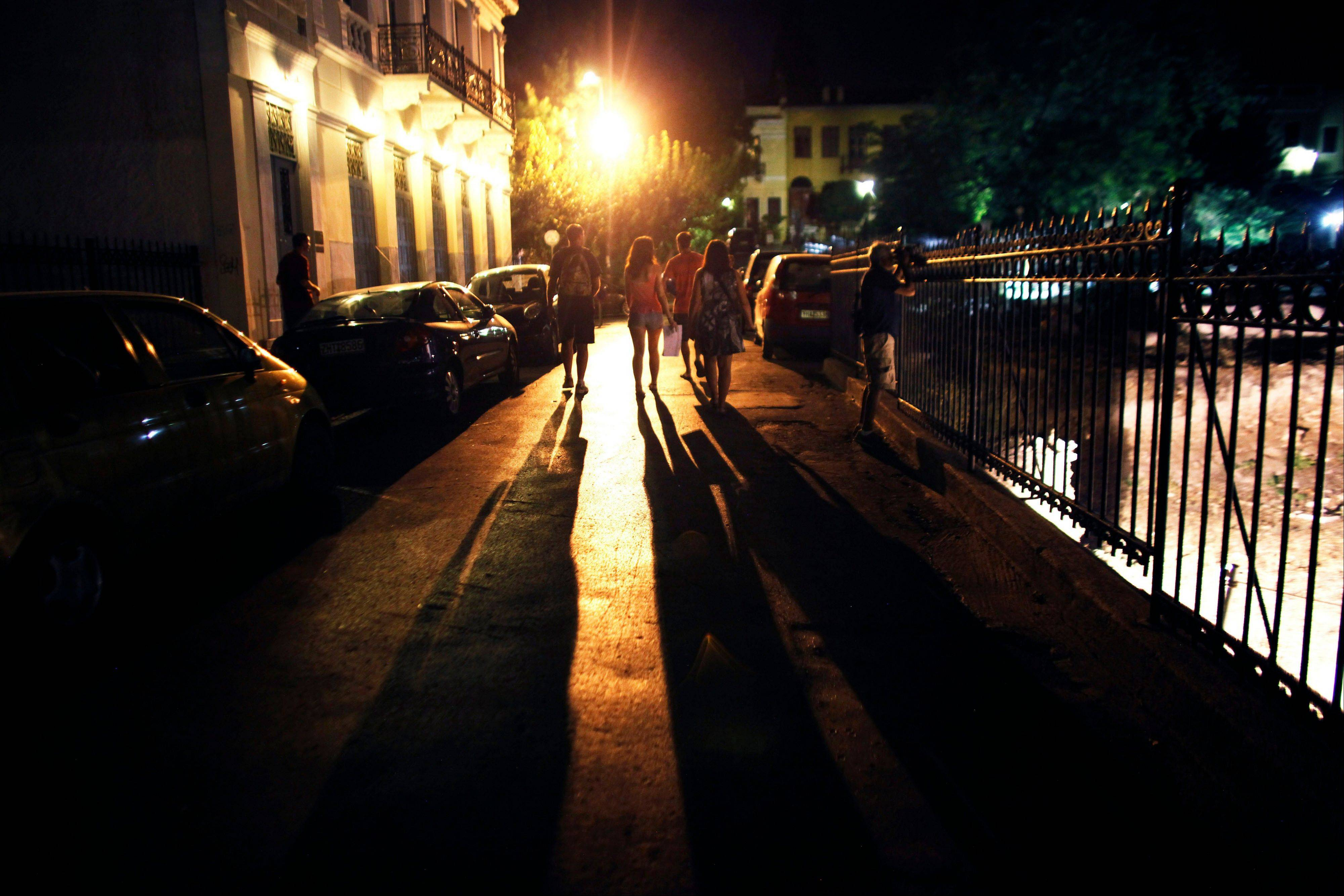 Pedestrians walk along a street illuminated by lights at night in the Plaka district of Athens, Greece.