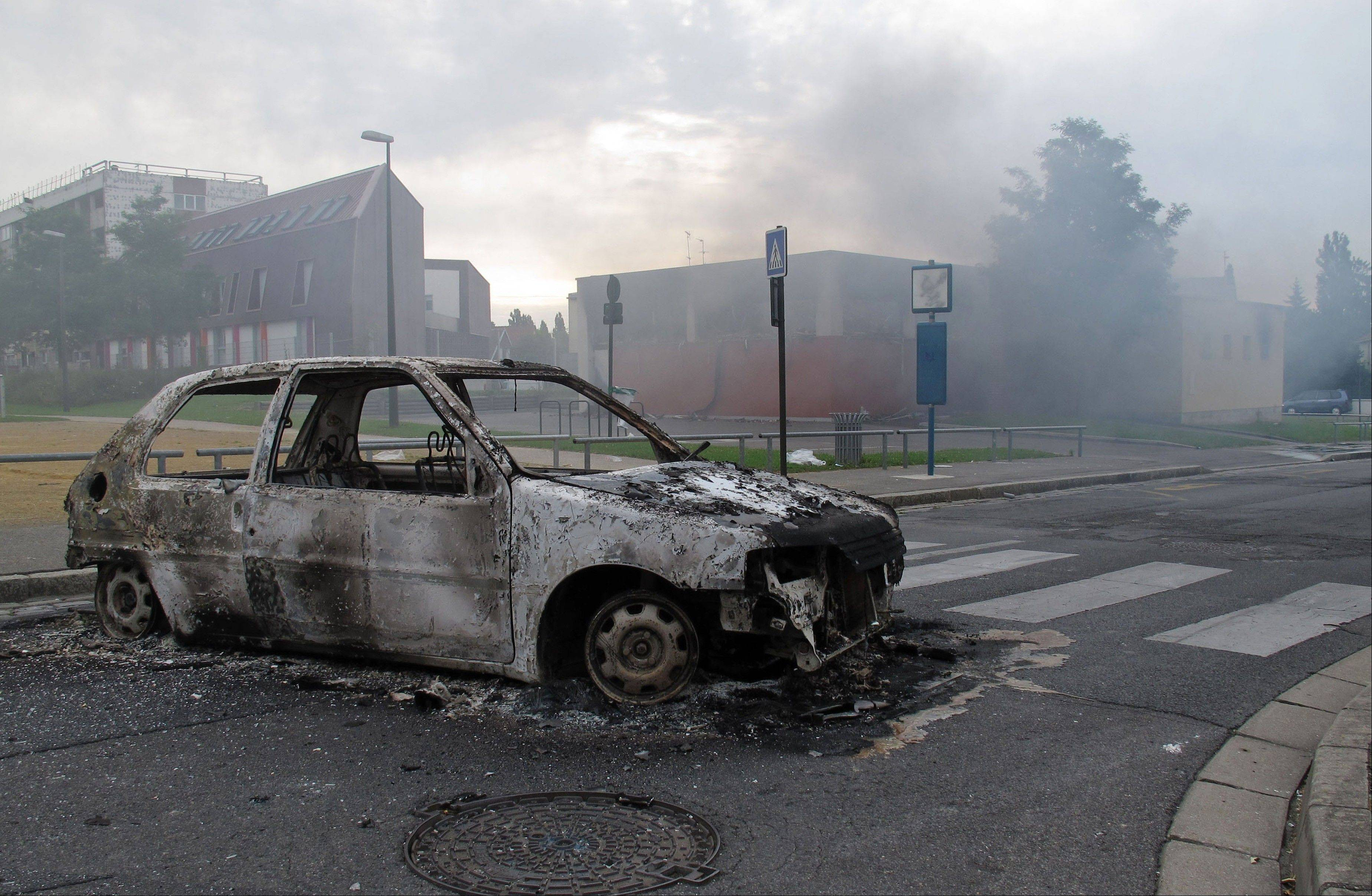 The shell of a burned out car is seen in a neighborhood of Amiens, France, Tuesday, Aug. 14, 2012. Dozens of young men rioted in a troubled district in northern France after weeks of tensions, pulling drivers from their cars and stealing the vehicles, and burning a school and a youth center. The police department in Amiens says at least 16 officers were hurt by the time the riot ended Tuesday, some by buckshot.