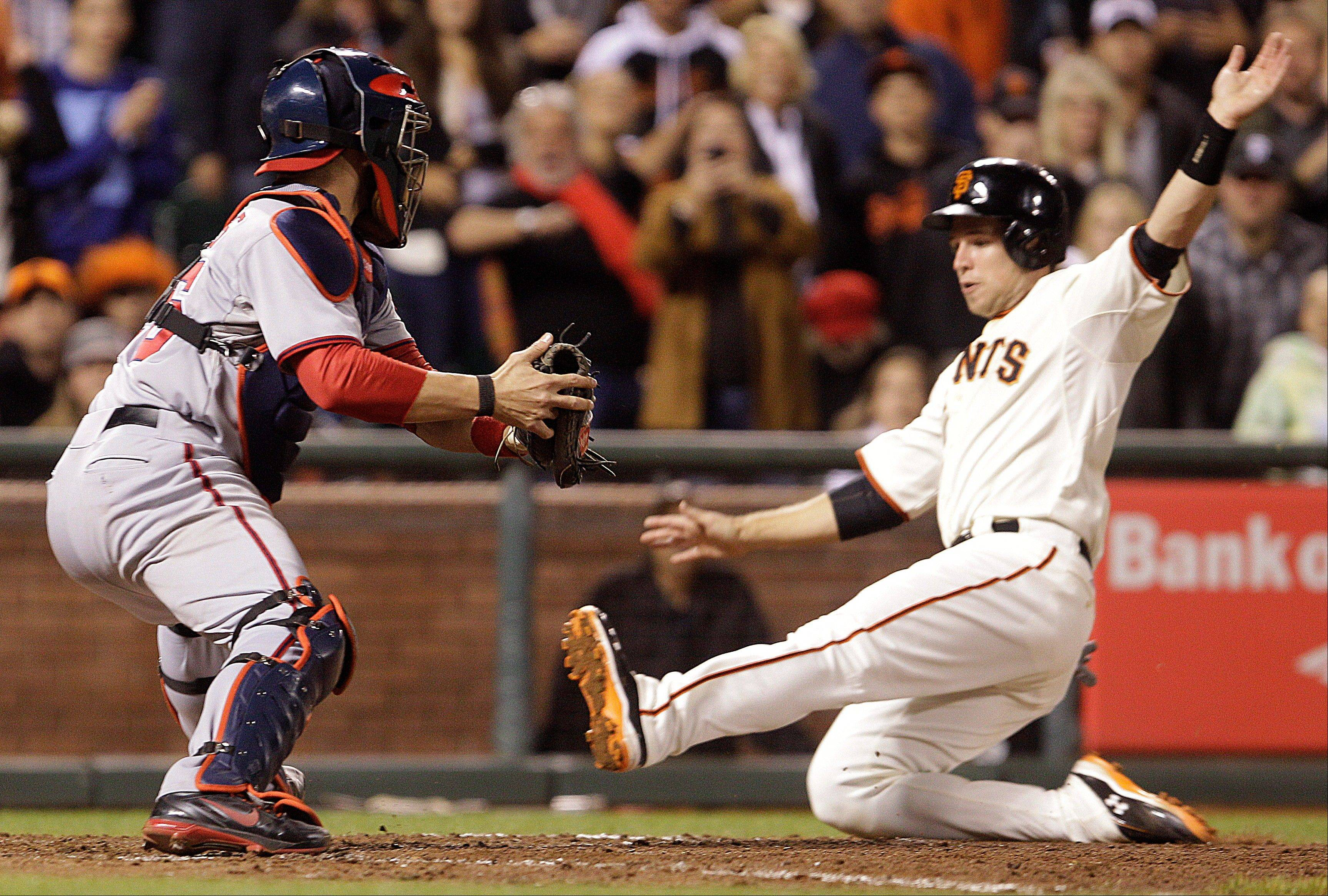 The Giants� Buster Posey slides in to score in front of Washington Nationals catcher Jesus Flores in the eighth inning Tuesday in San Francisco. Posey scored on a single by Brandon Belt.