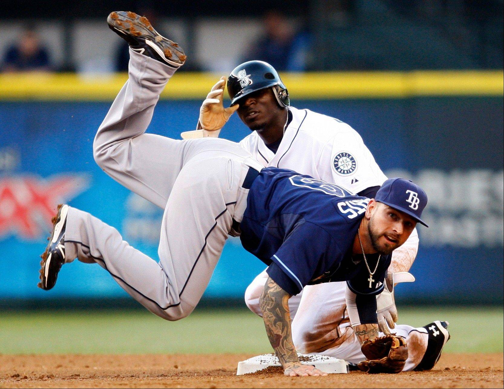 Tampa Bay second baseman Ryan Roberts jumps over the Mariners� Trayvon Robinson as he completes his throw to first base for a double play Tuesday night in Seattle.