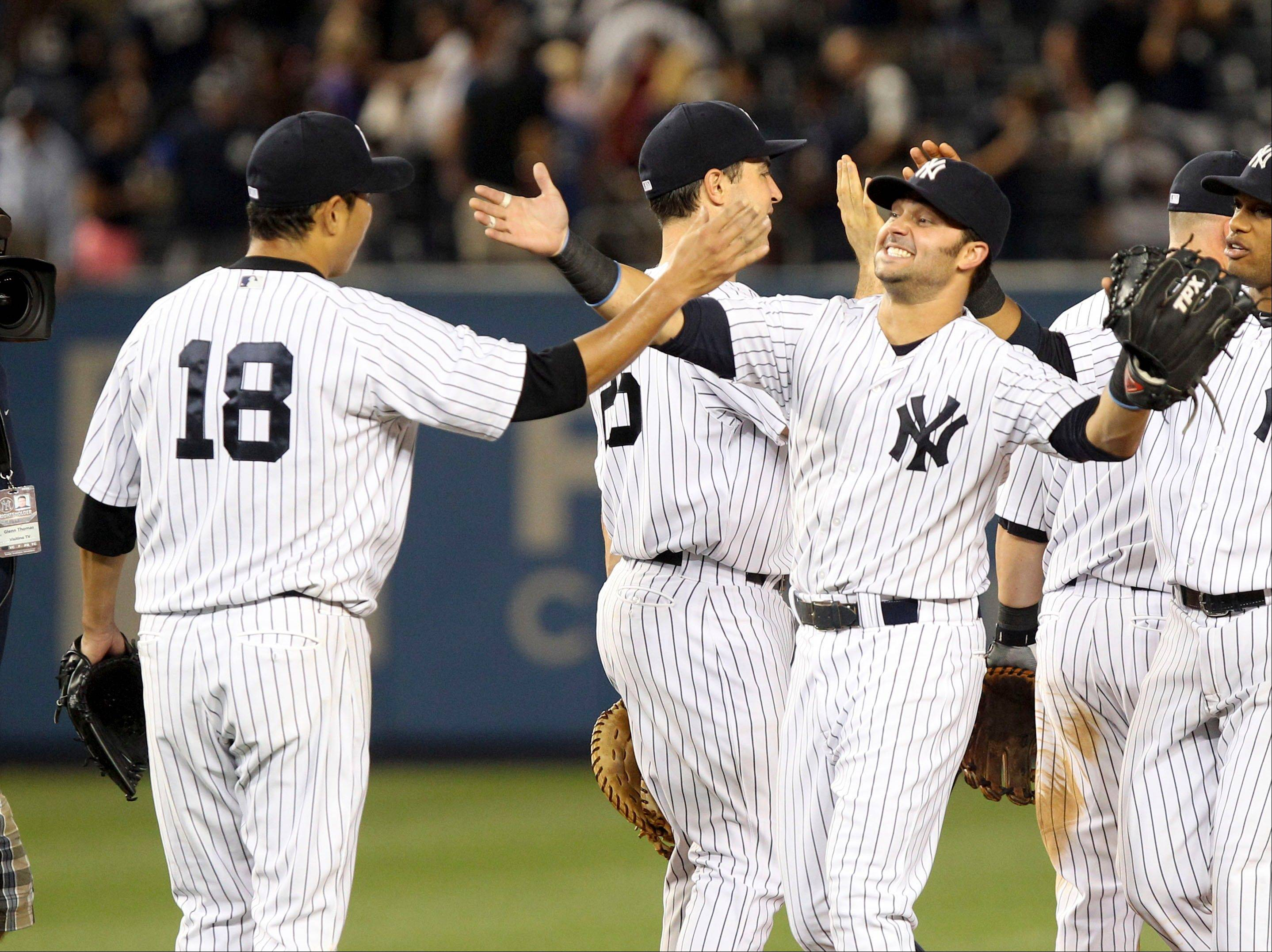 The New York Yankees� Nick Swisher, right, greets pitcher Hiroki Kuroda after Kuroda threw a two-hitter Tuesday against the Texas Rangers at Yankee Stadium in New York. The Yankees won 3-0.