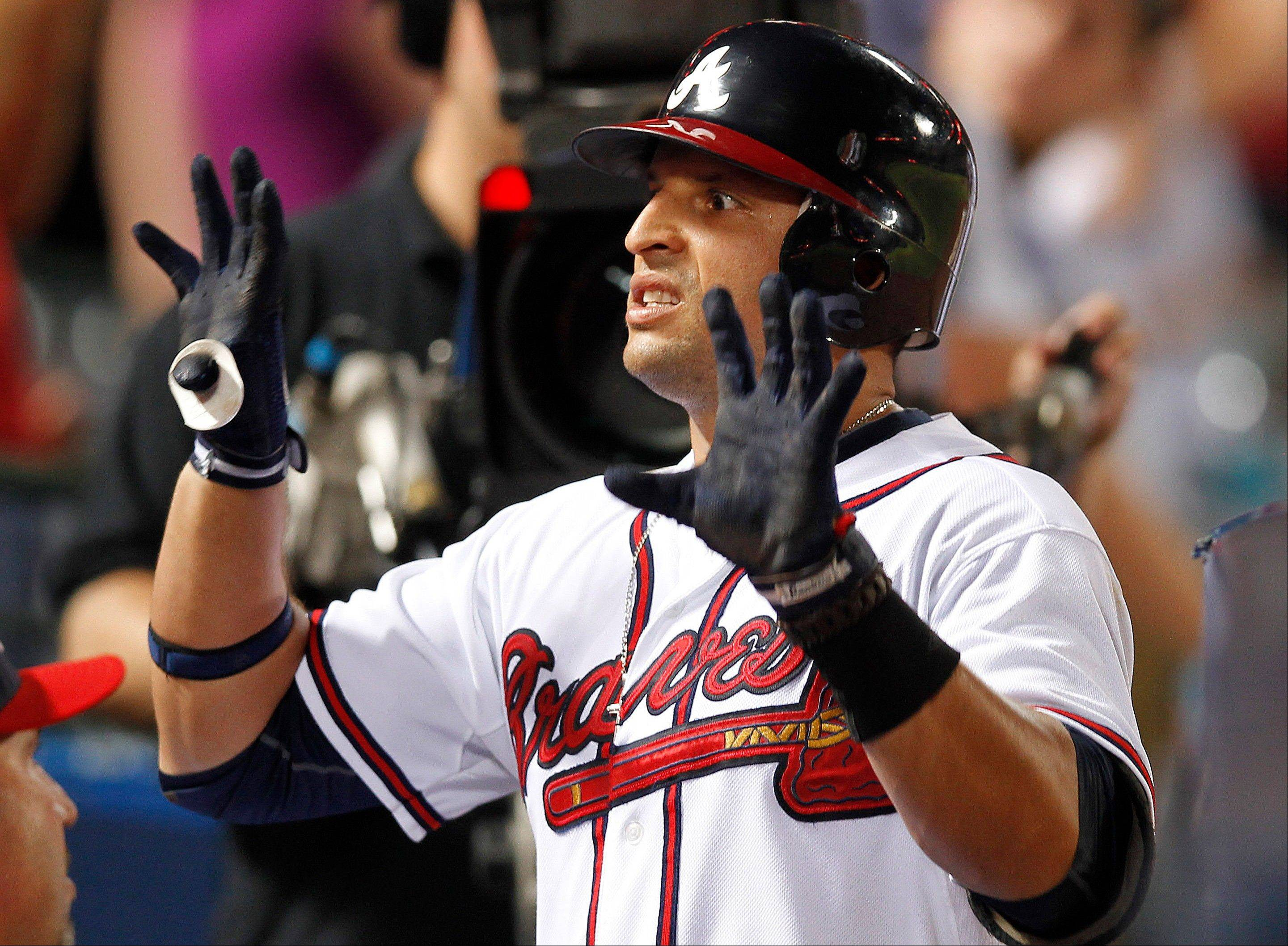 The Atlanta Braves� Martin Prado celebrates in the dugout after hitting a three-run home run Tuesday during the seventh inning.