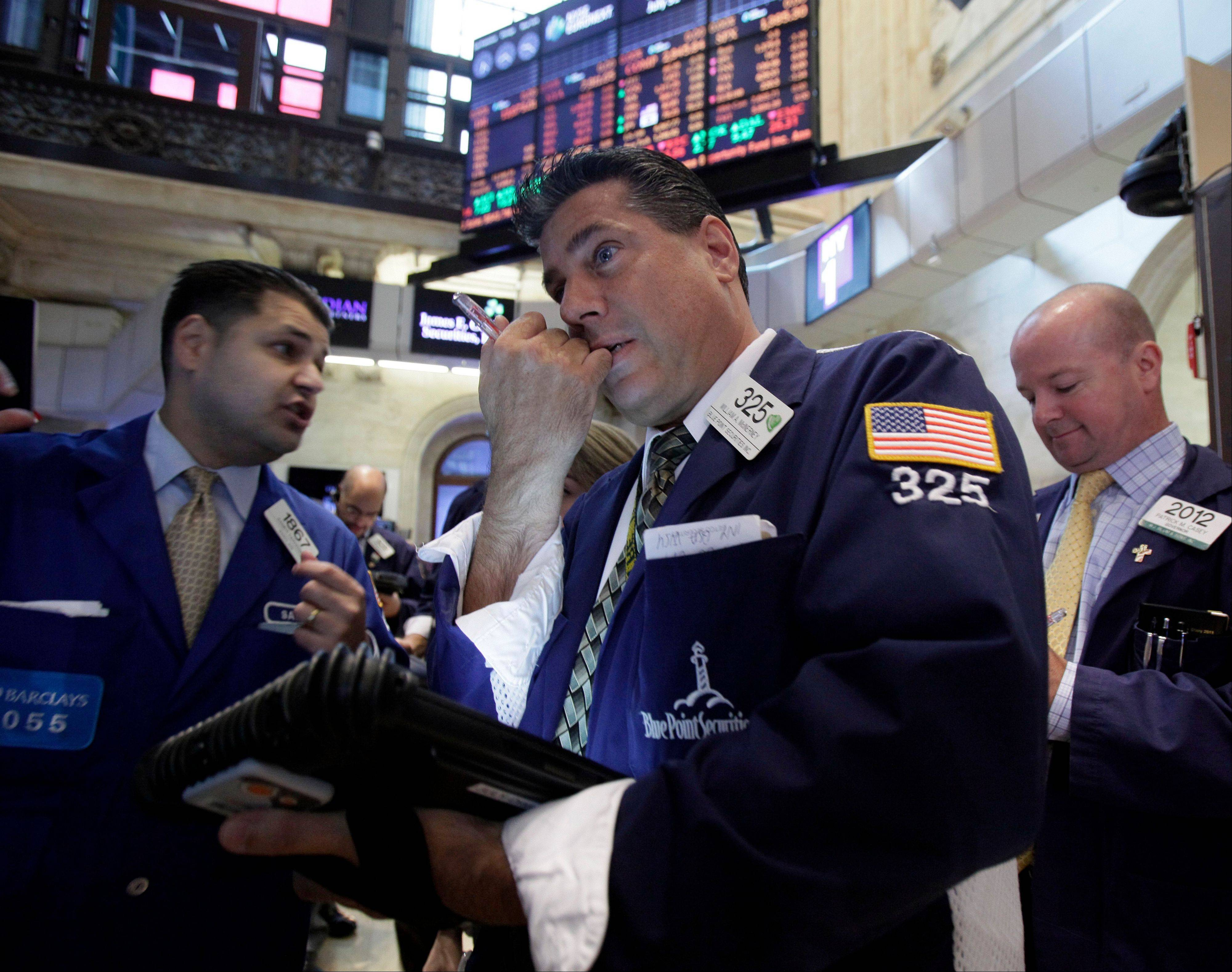 Trader William McInerney, center, works on the floor of the New York Stock Exchange. U.S. stocks fell Monday as evidence piled up that the global economic slowdown is dragging on Asia.