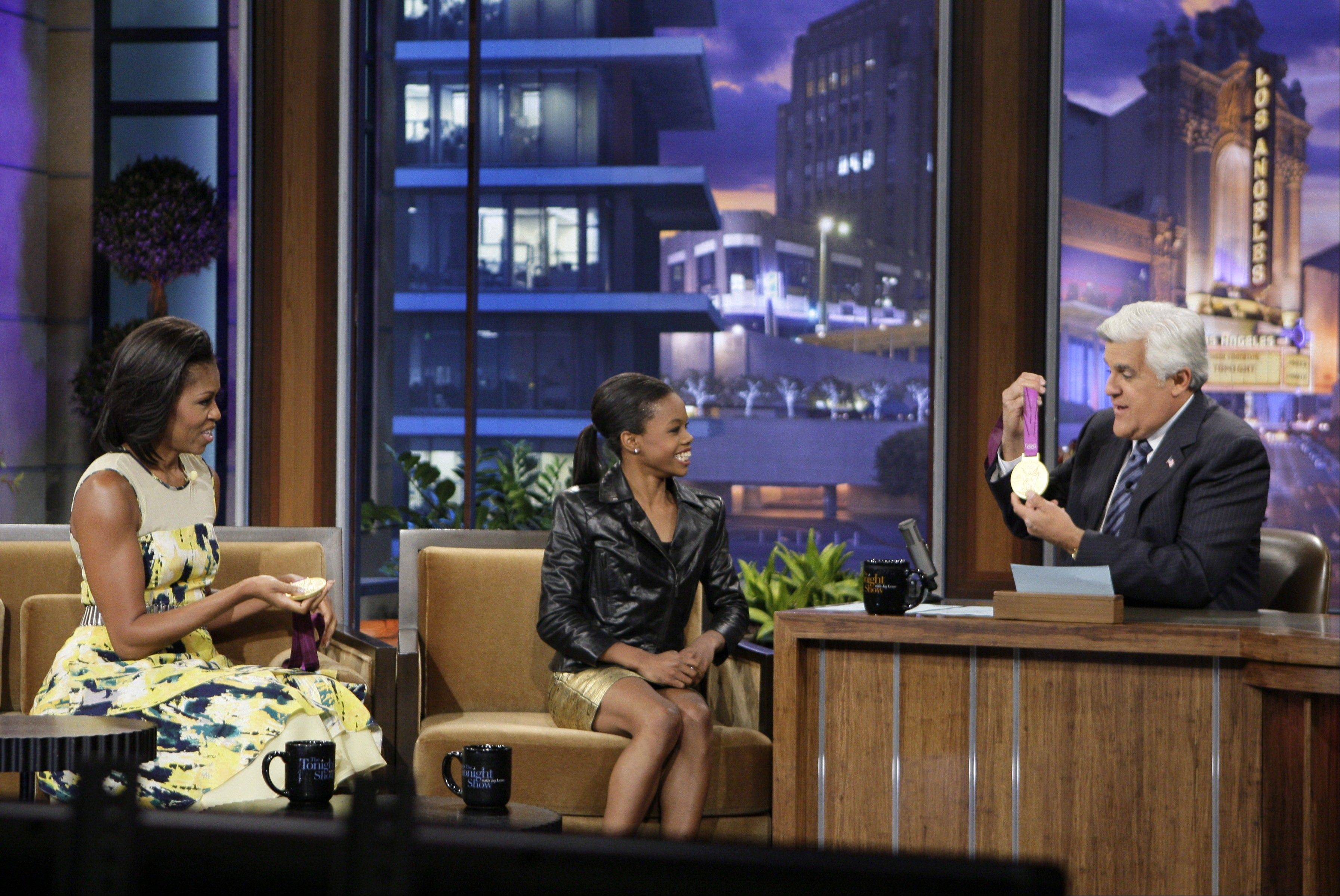 "First lady Michelle Obama, left, Olympic gold medalist Gabby Douglas and host Jay Leno chat Monday during a taping of ""The Tonight Show with Jay Leno."""