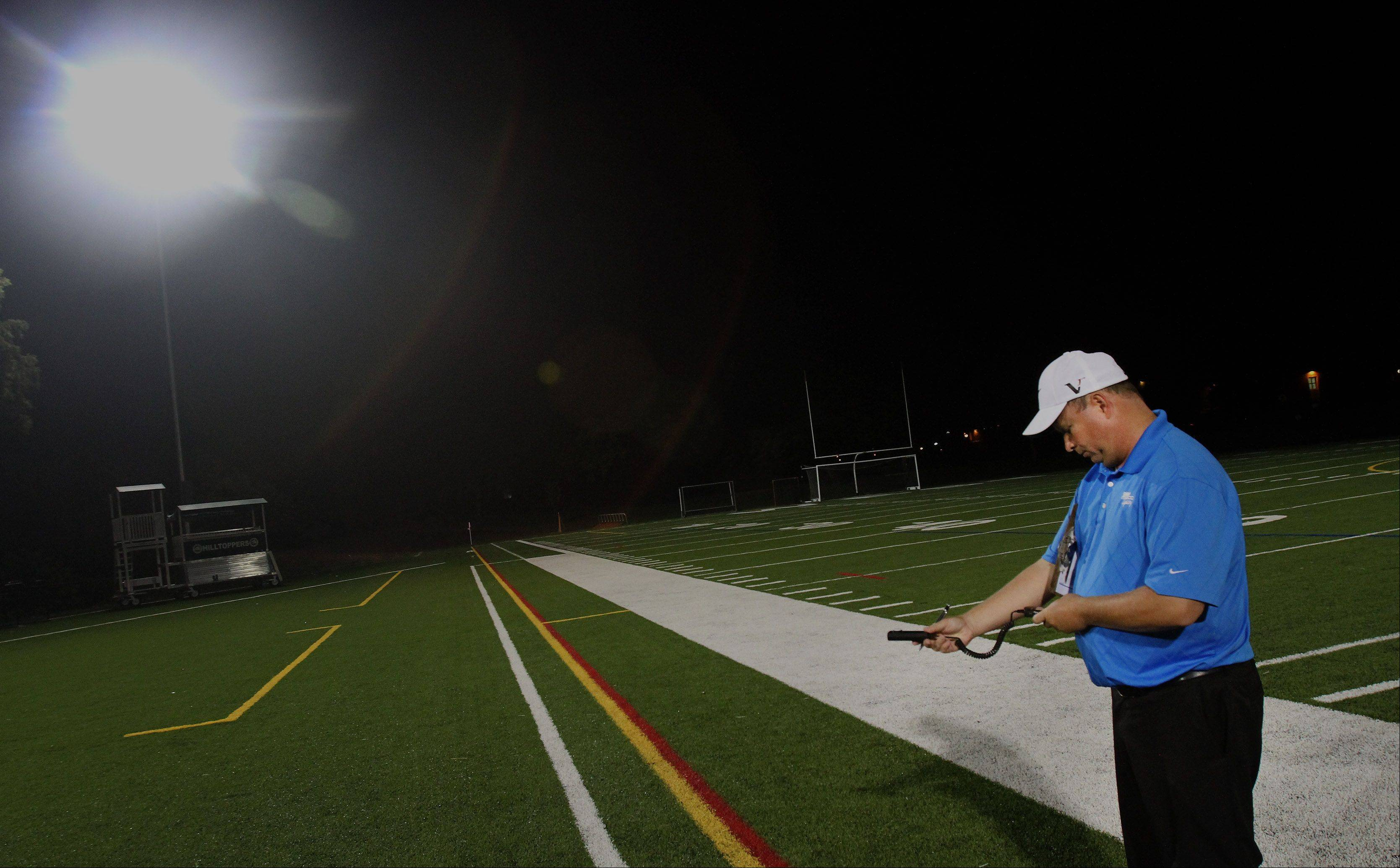 David Miller of Musco Lighting takes a reading during a test of the new lights Monday at Memorial Field in Glen Ellyn.