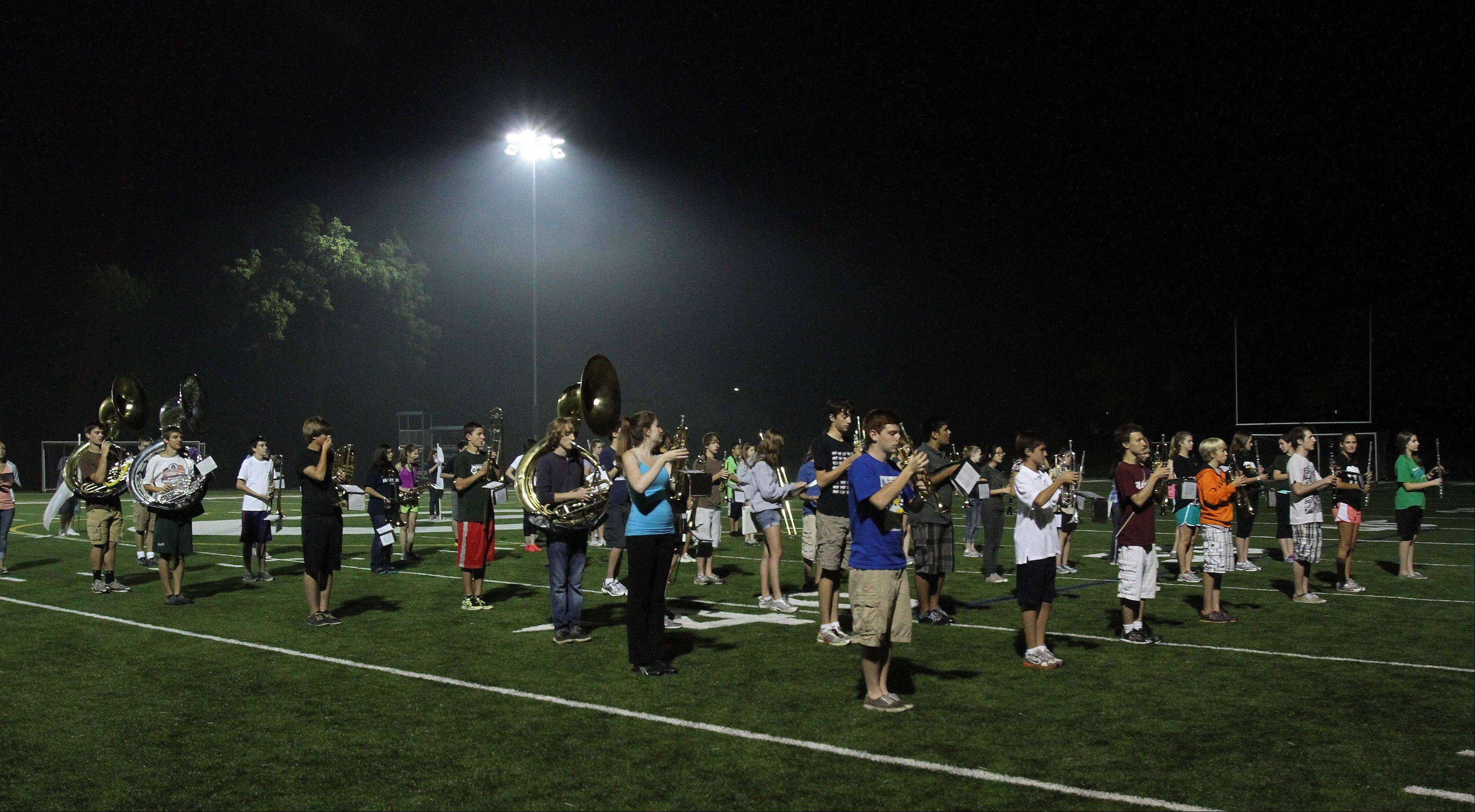 The Glenbard West High School marching band practices Monday night at Memorial Field in Glen Ellyn as officials tested the field's new lighting system for the first time.
