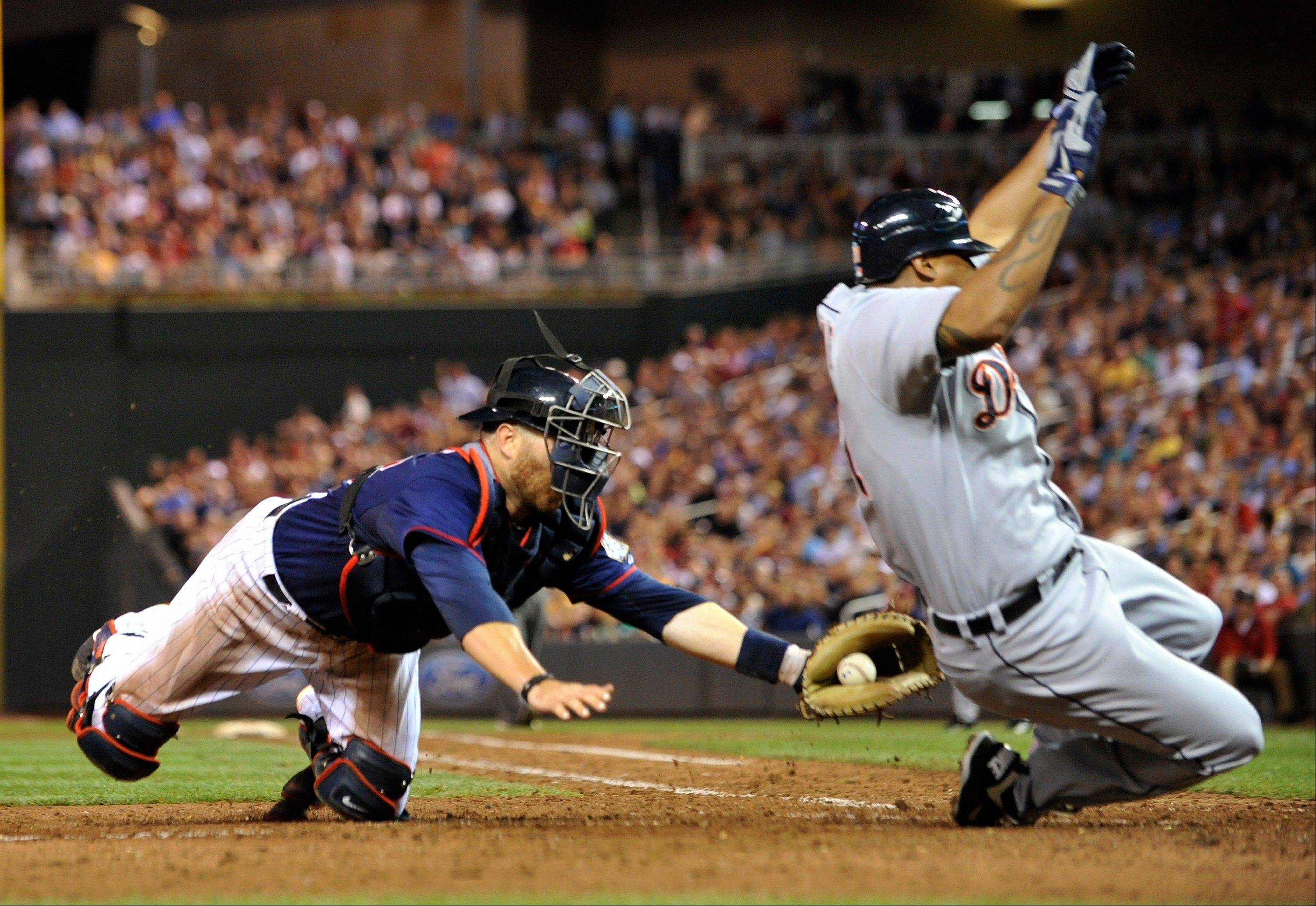 Minnesota Twins catcher Ryan Doumit, left, tags out the Detroit Tigers' Delmon Young as he tries to score from second on a single by Gerald Laird Tuesday during the eighth inning in Minneapolis.