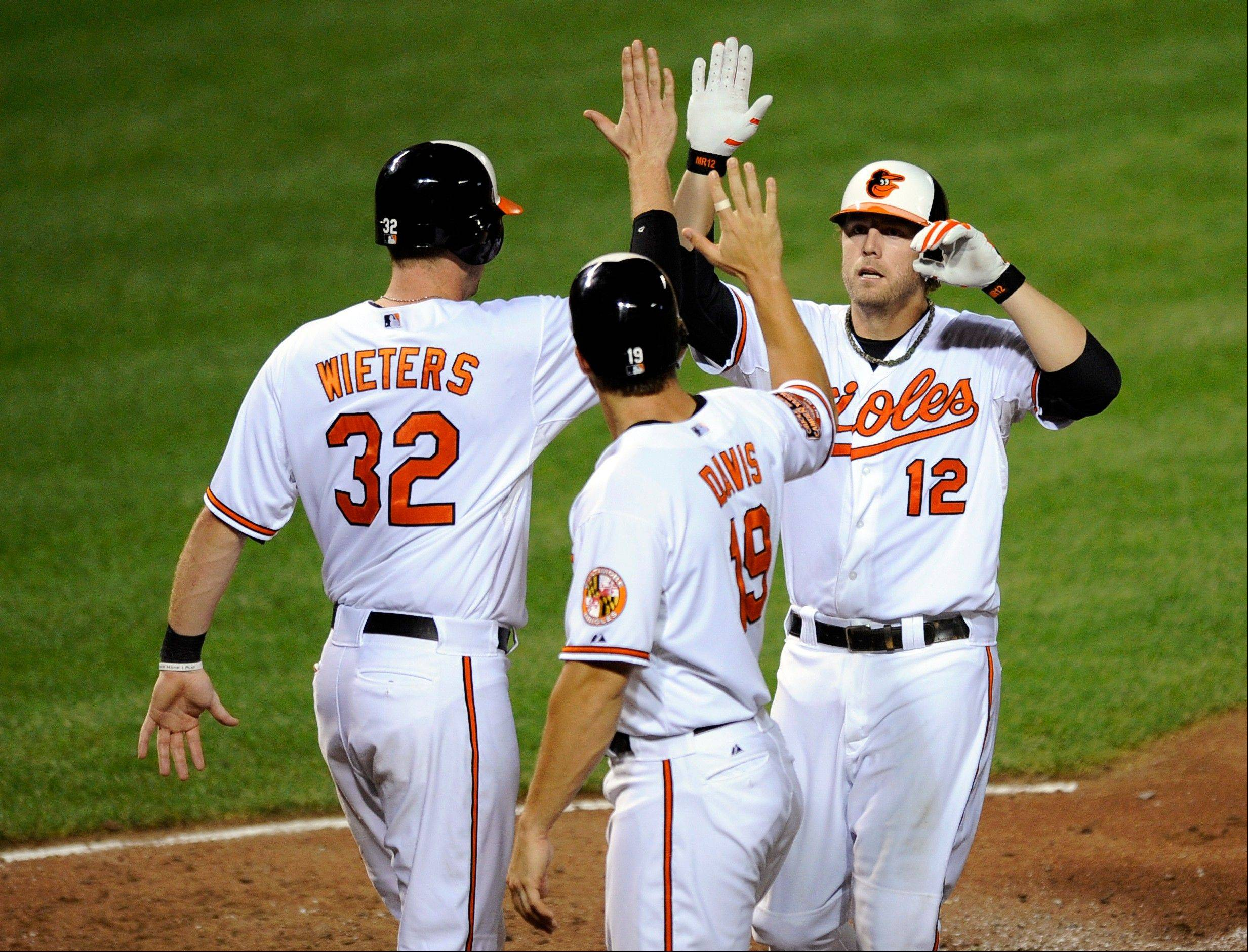 The Baltimore Orioles' Mark Reynolds (12) celebrates his three-run home run with Matt Wieters (32) and Chris Davis (19) Tuesday during the sixth inning against the Boston Red Sox.