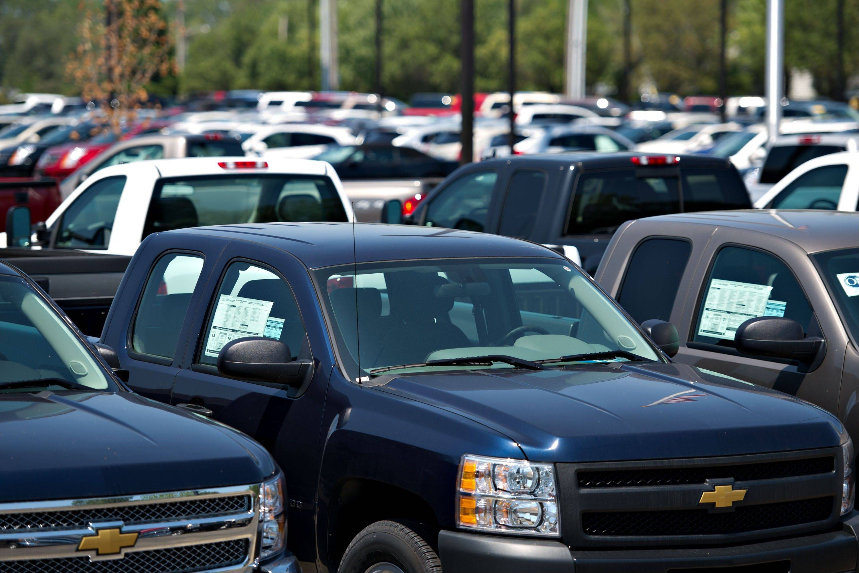 Chevy Silverado pickup trucks sit on display at a General Motors Co. dealership in Peoria.