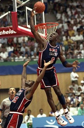 In this July 27, 1992 file photo, USA's Michael Jordan sails high above teammate Magic Johnson knocking away a shot during the first half of their preliminary round basketball game with Croatia at the Summer Olympics in Barcelona.