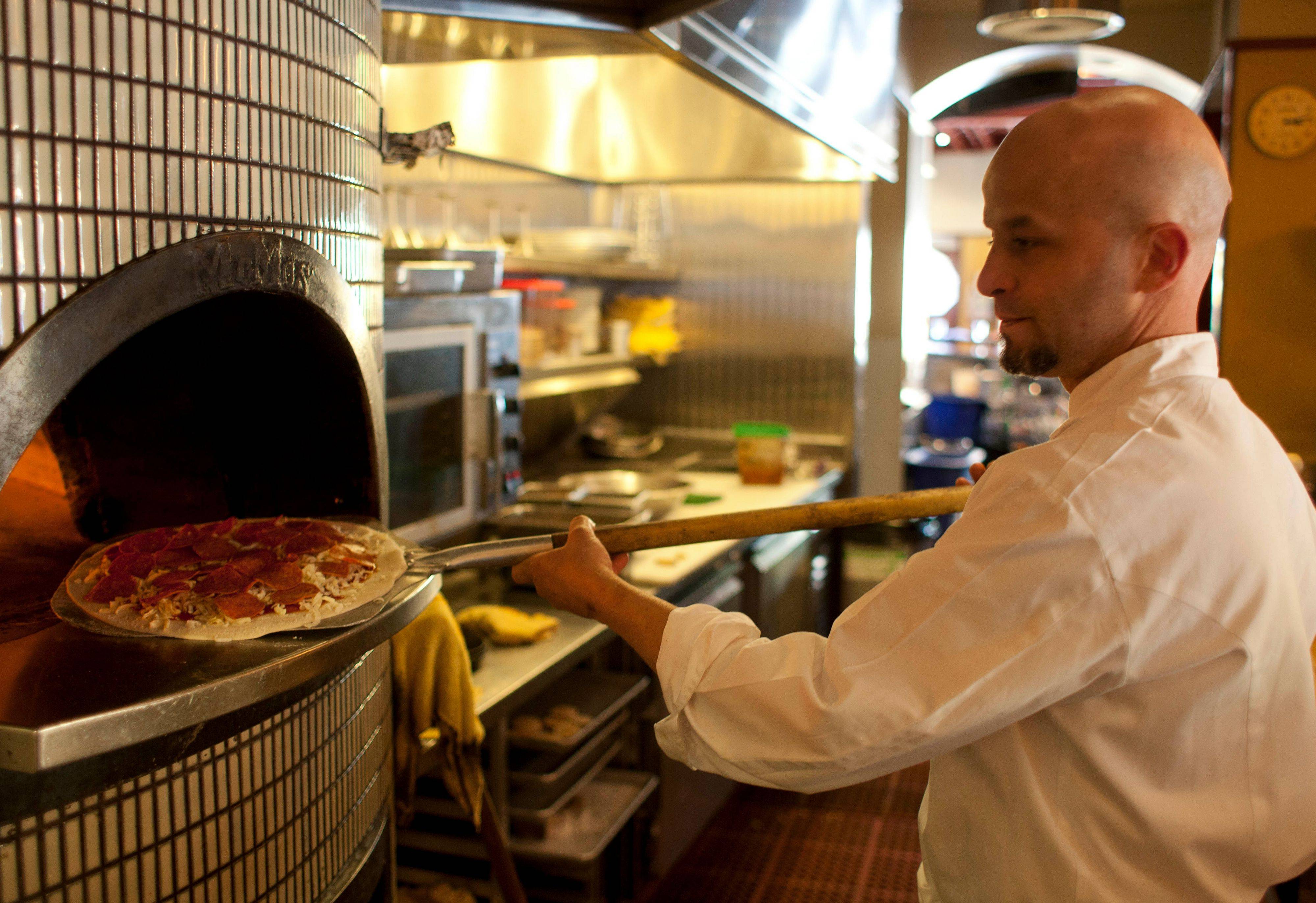 Chef Damon Hall puts a pepperoni pizza into an oven at MoMo's restaurant in San Francisco. With a wood-burning oven at MoMo's, Hall can more than banish the ghosts of pizzas past using fresh seasonings to kick up the taste.
